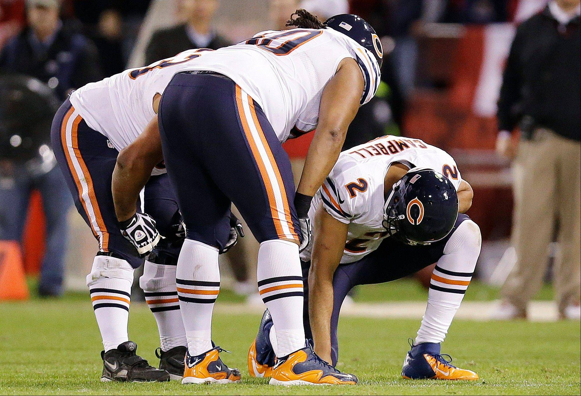 Chicago Bears quarterback Jason Campbell is looked over by teammates after being tackled during the second half.