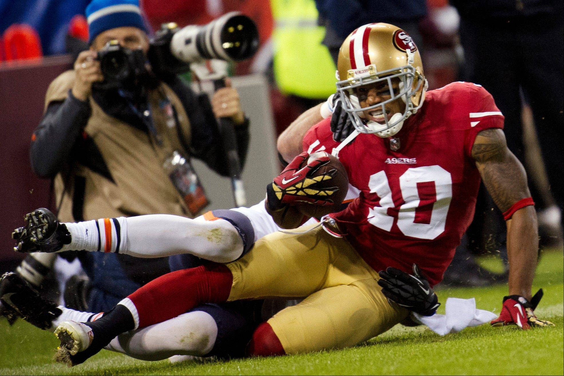 San Francisco 49ers wide receiver Kyle Williams is tackled by Chicago Bears free safety Chris Conte, obscured, near the goal line after a pass reception during the first quarter .