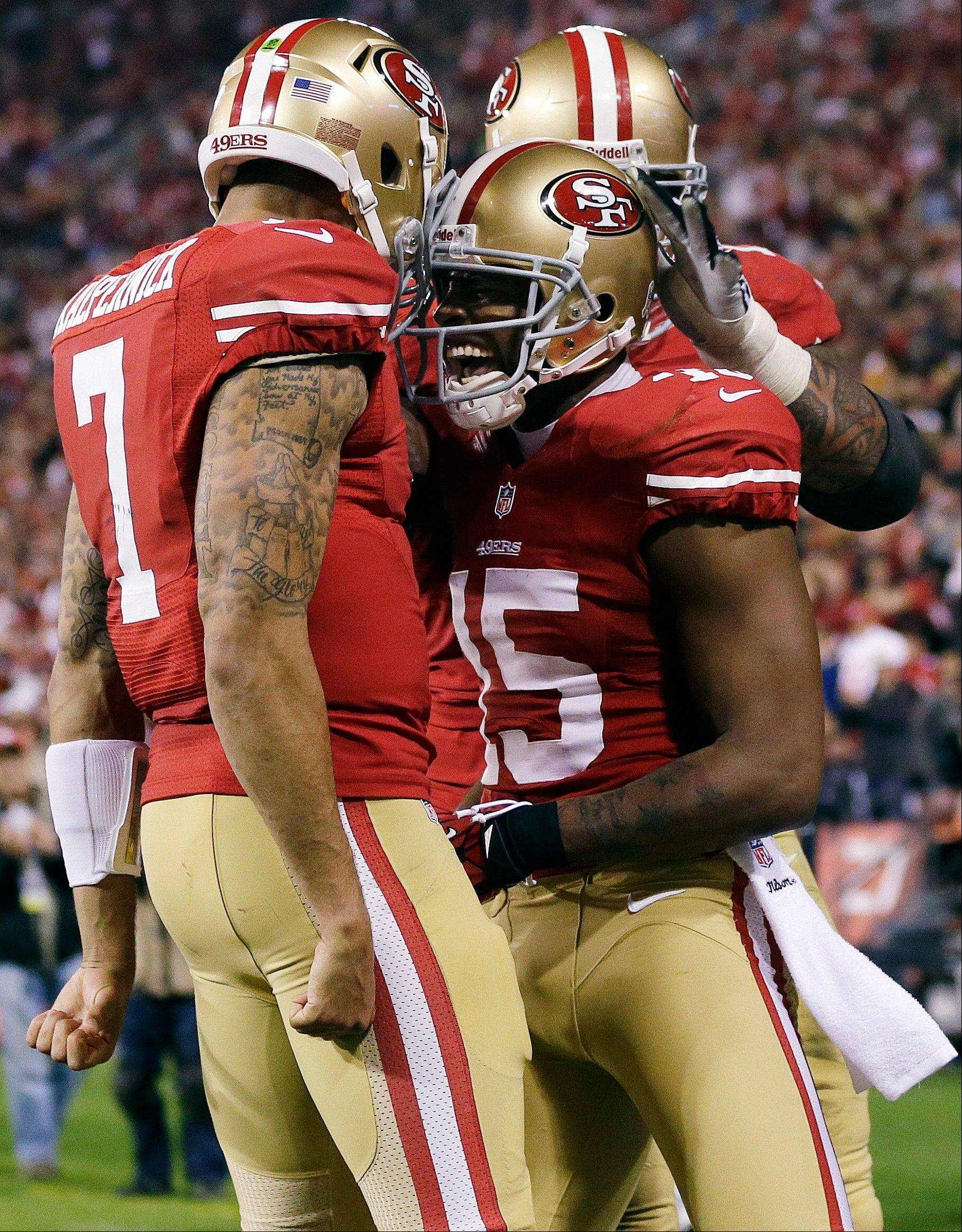 San Francisco 49ers wide receiver Michael Crabtree celebrates with quarterback Colin Kaepernick and guard Mike Iupati after scoring on a 10-yard touchdown reception.