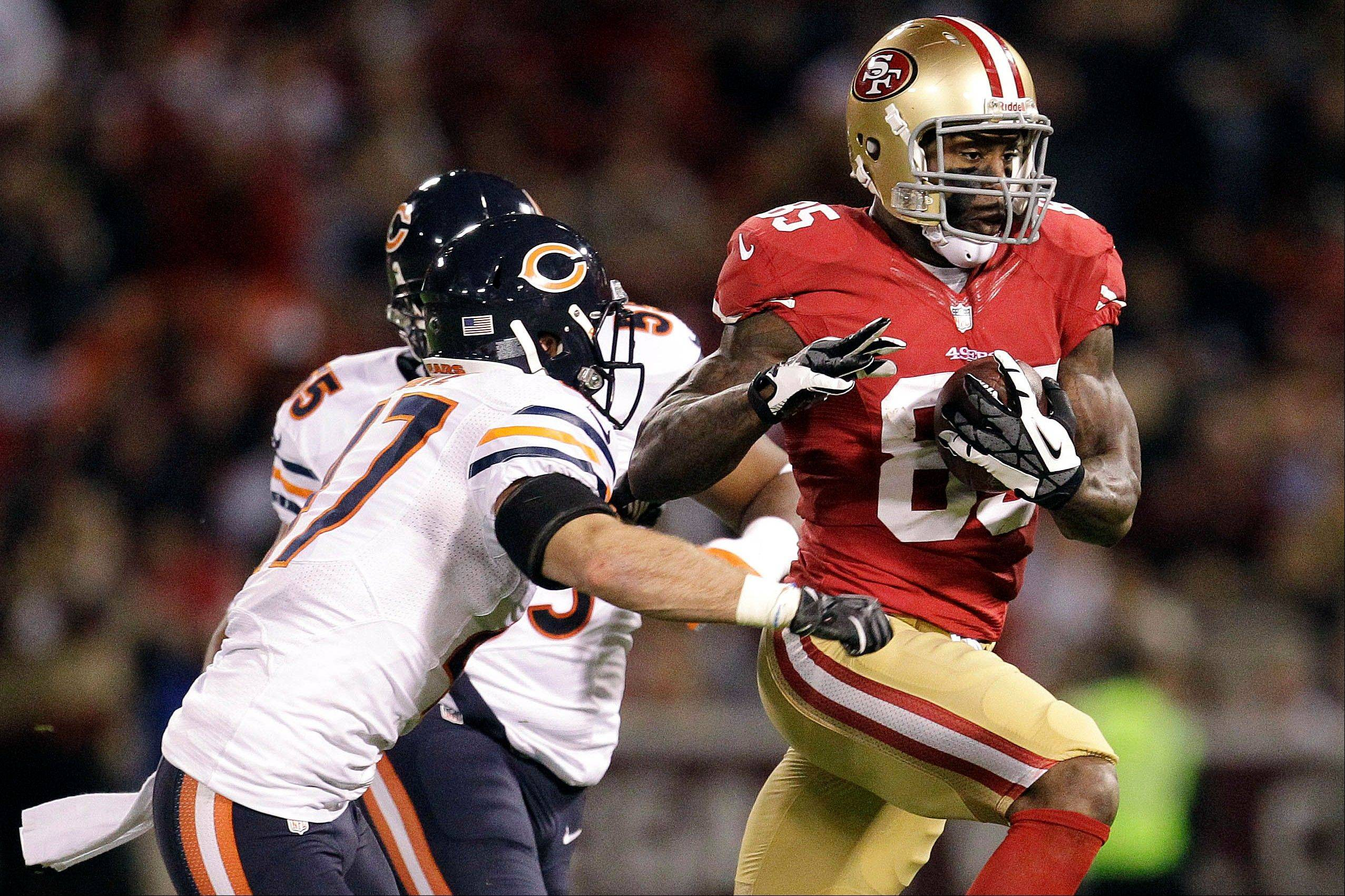 San Francisco 49ers tight end Vernon Davis runs with a pass against Chicago Bears free safety Chris Conte and outside linebacker Lance Briggs during the first half.