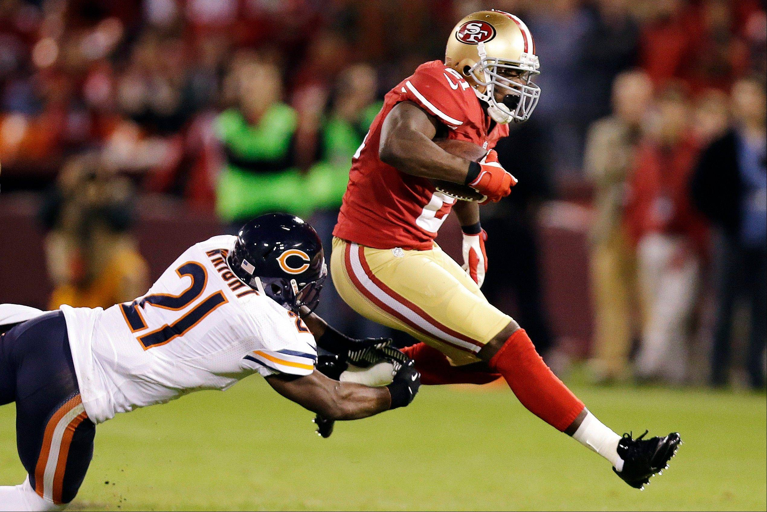 San Francisco 49ers running back Frank Gore jumps past Chicago Bears strong safety Major Wright during the second quarter.