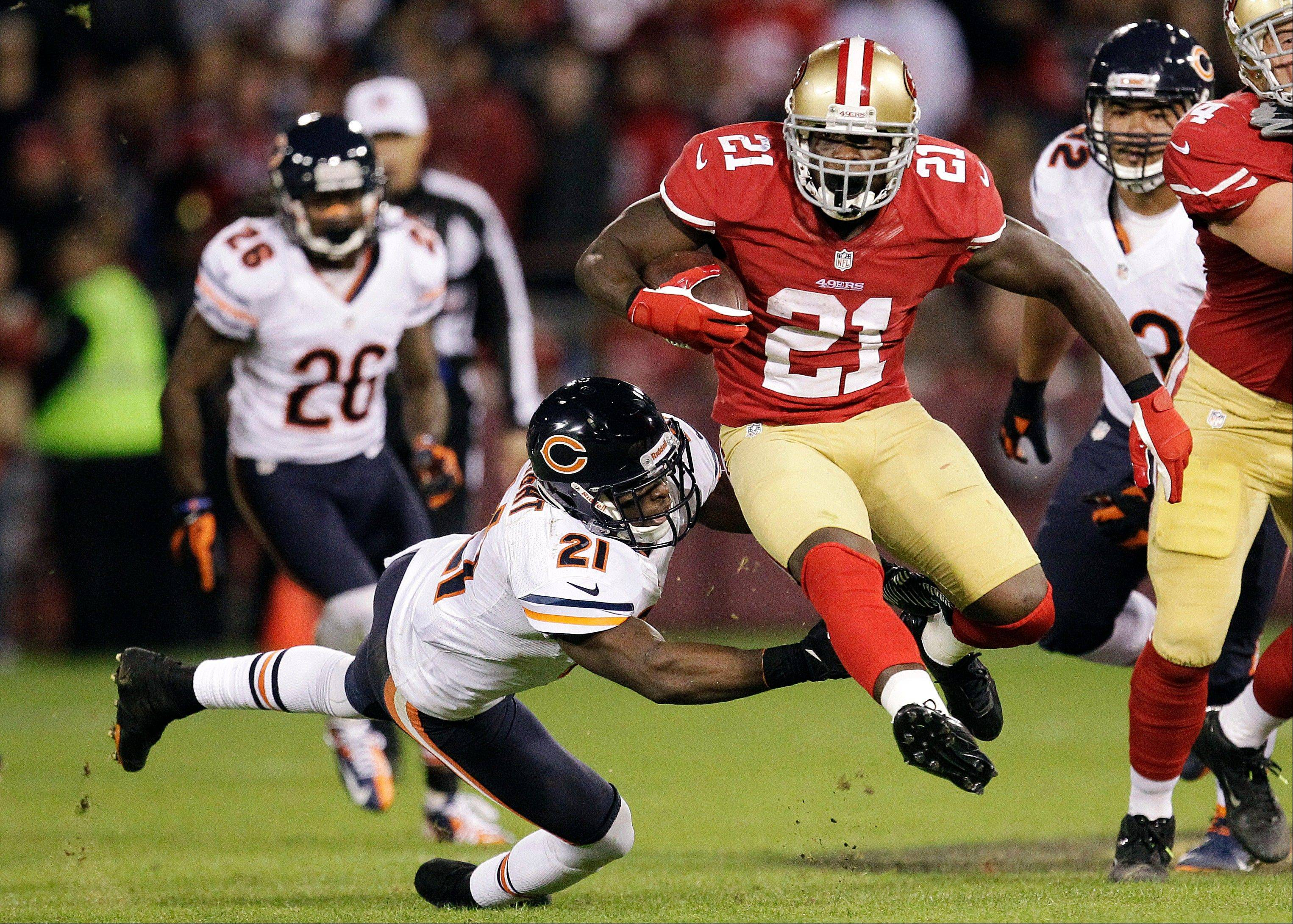 San Francisco 49ers running back Frank Gore leaps past Chicago Bears strong safety Major Wright during the second quarter.