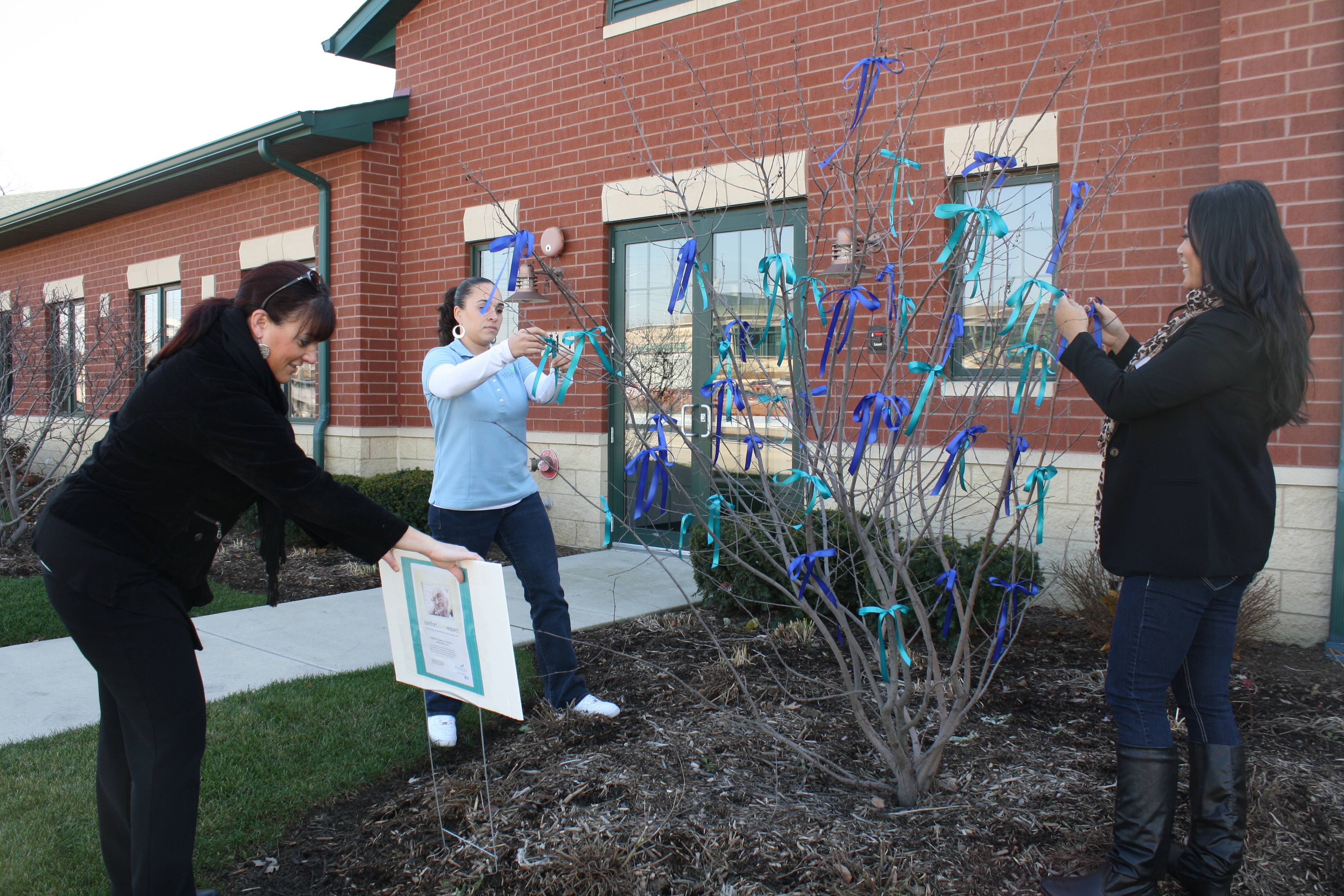 From left to right: Stacy Barclay, Carmen Velez, and Tina Prasanesouk of Passages Hospice tie ribbon to the tree outside the Passages Hospice office in Lisle in support of National Hospice Month on November 16th.