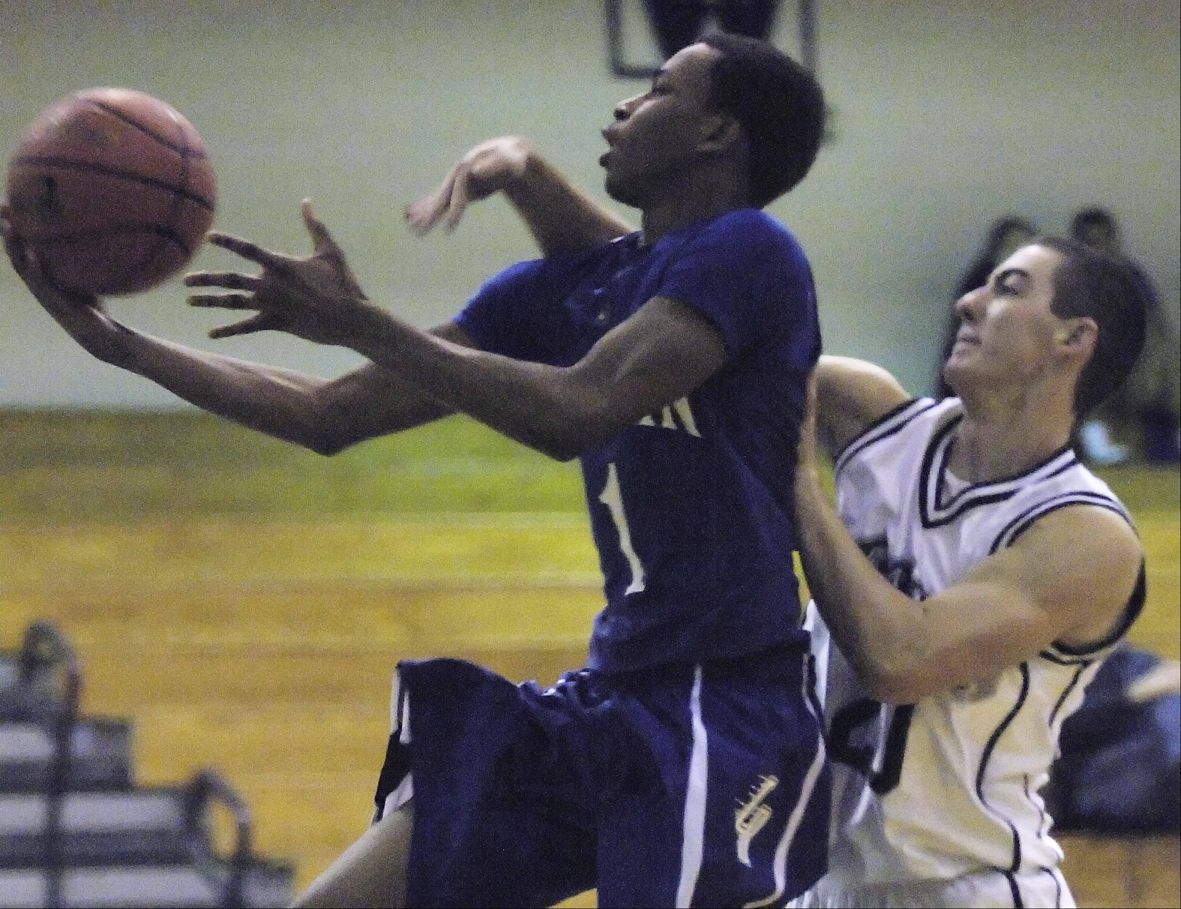 Cary-Grove�s Clay Marunde fouls Larkin�s Quantice Hunter Tuesday in the Hoops for Healing Tournament in Woodstock.