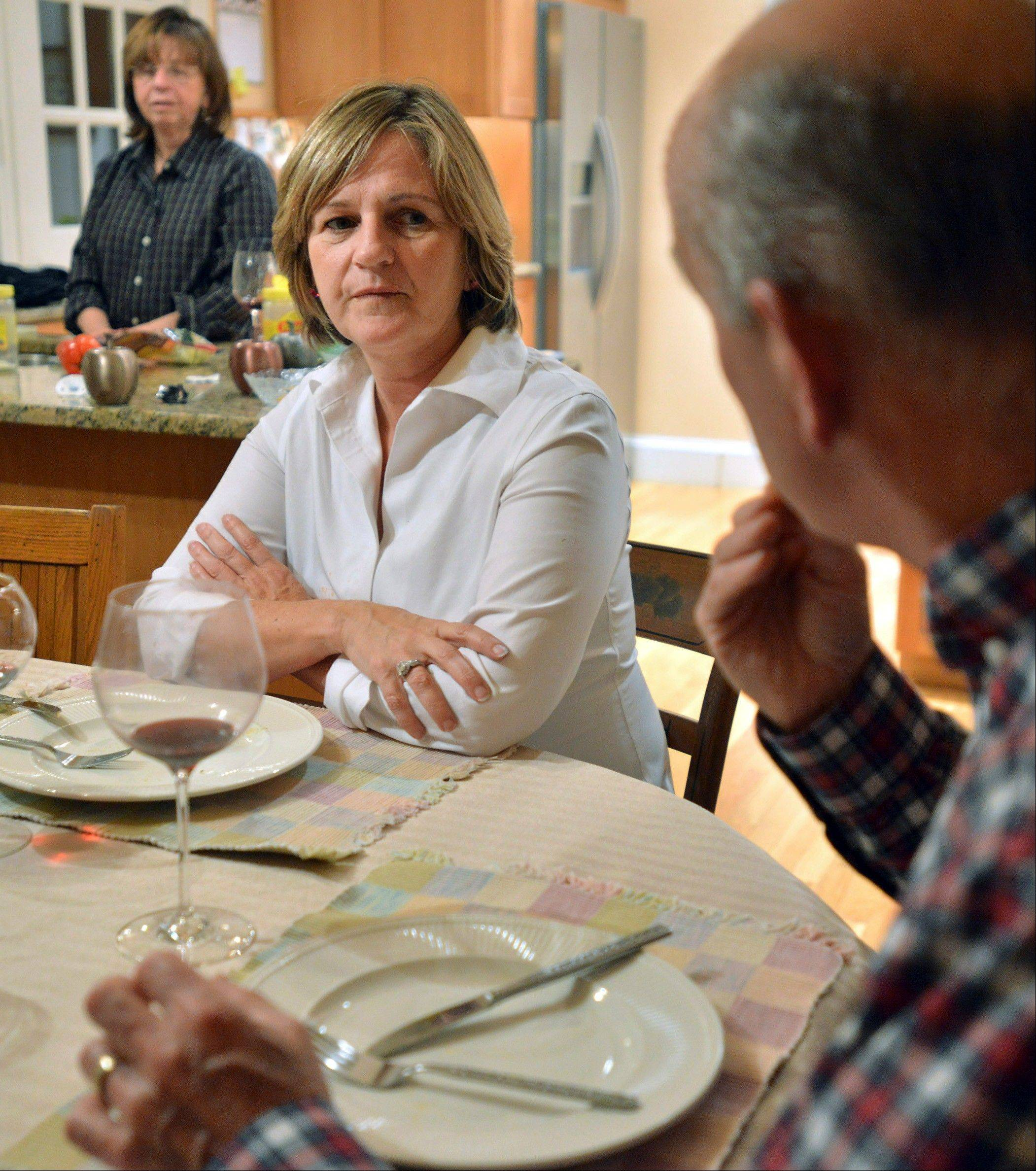 Anne Brennan, center, of Hingham Mass., listens to her sister, Linda Marshall, rear, and brother-in-law Steve Marshall, right, discuss the recent presidential election as the family gathers for dinner in Hingham and where politics are a frequent -- and divisive -- topic of conversation.