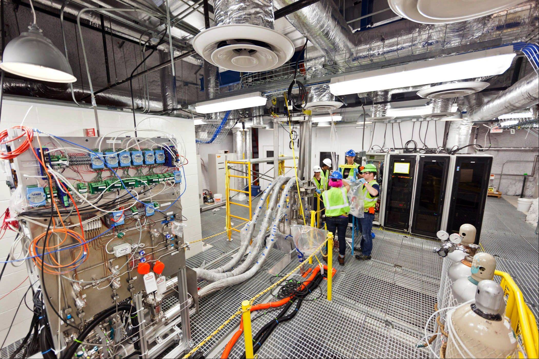 Researchers work on the top floor of the Large Underground Xenon experiment at a shuttered gold mine in Lead, S.D. The experiment, known as LUX, could begin collecting data on dark matter as early as February.