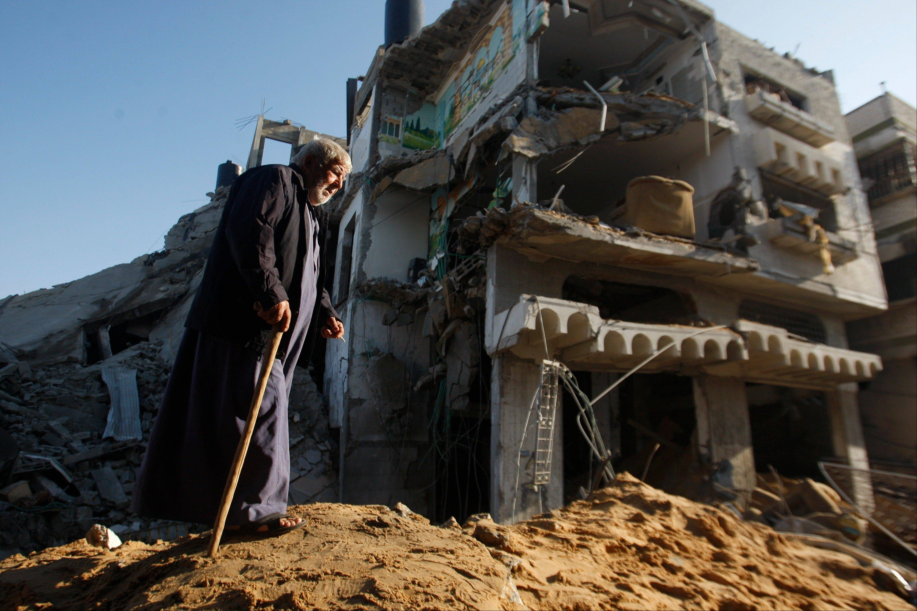 An elderly Palestinian walks next to a destroyed building after an Israeli strike in Gaza City, Tuesday, Nov. 20, 2012.