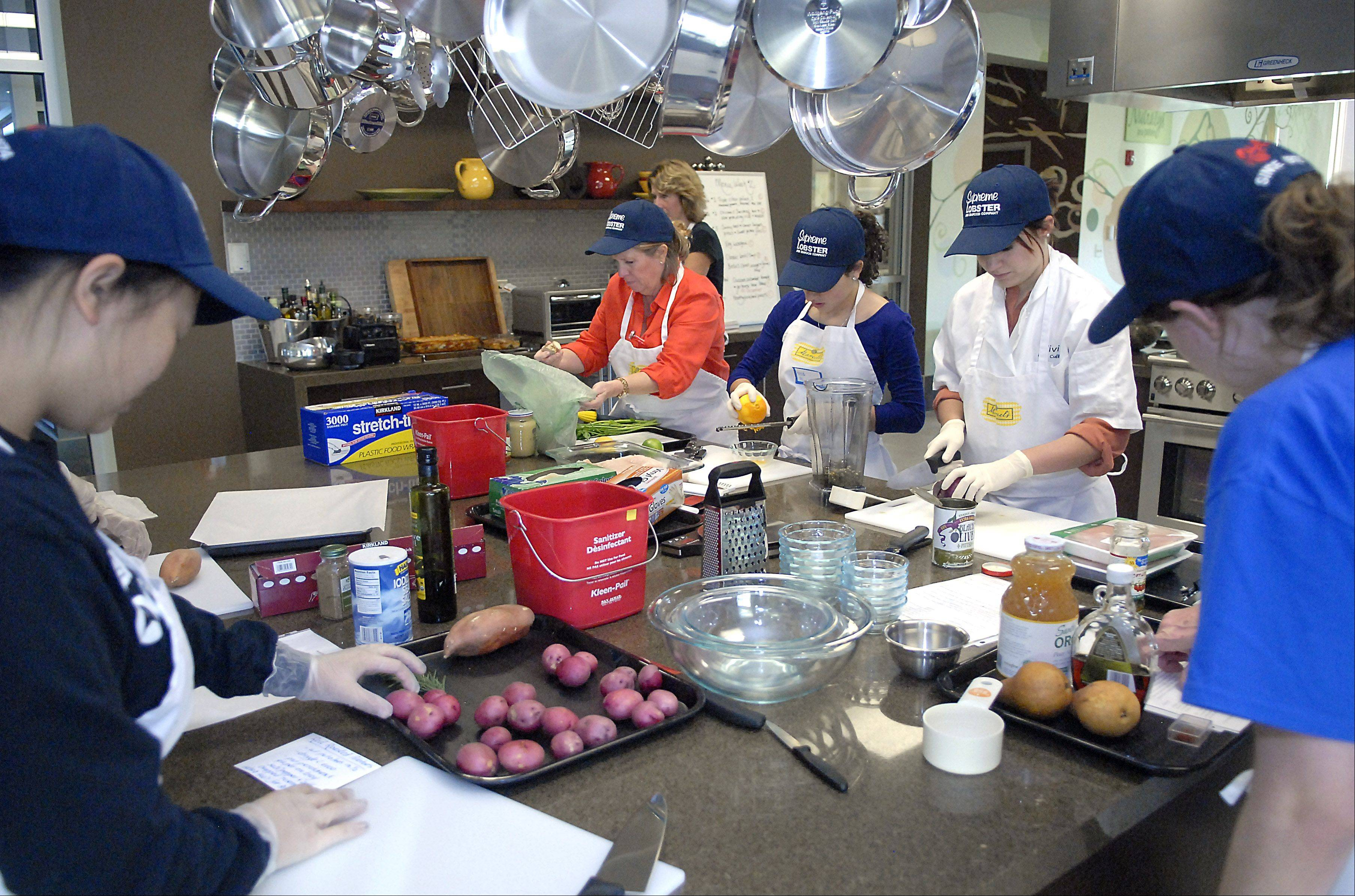 Nutritionist and program director Mary Fremgen, center, works with Geneva High School students in the Roquette America kitchen in Geneva. Students prepare meals for people with life-threatening illnesses registered with Fox Valley Food for Health.