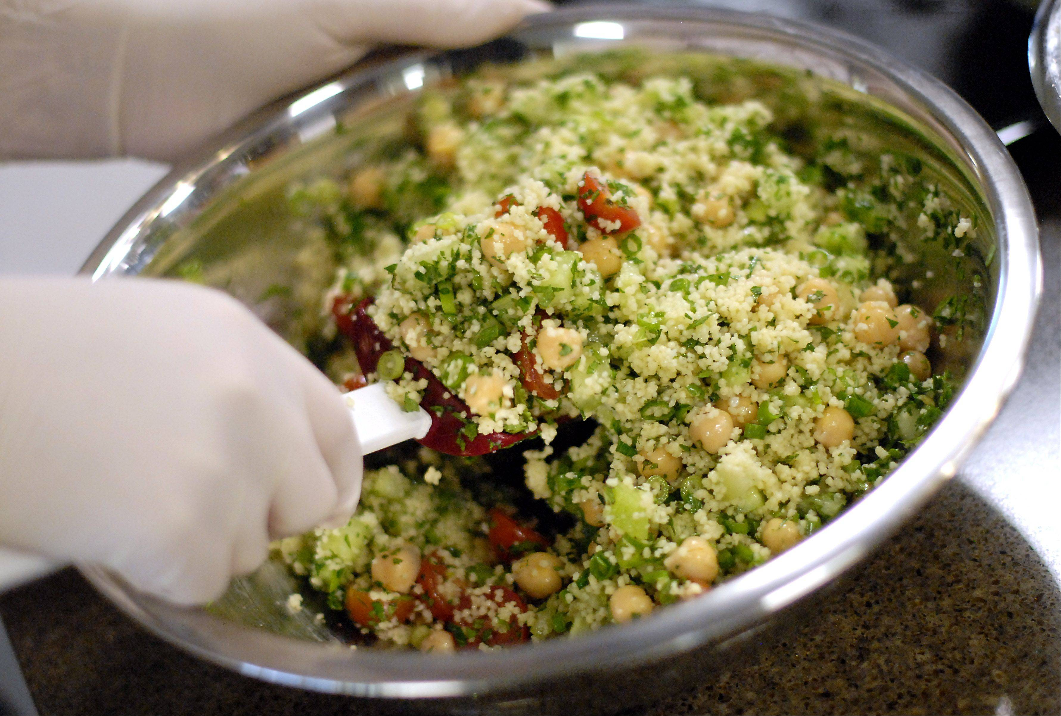 A couscous salad is mixed in the Roquette kitchen in Geneva. The meals are all plant-based, although they do include chicken or fish, and are healthy.