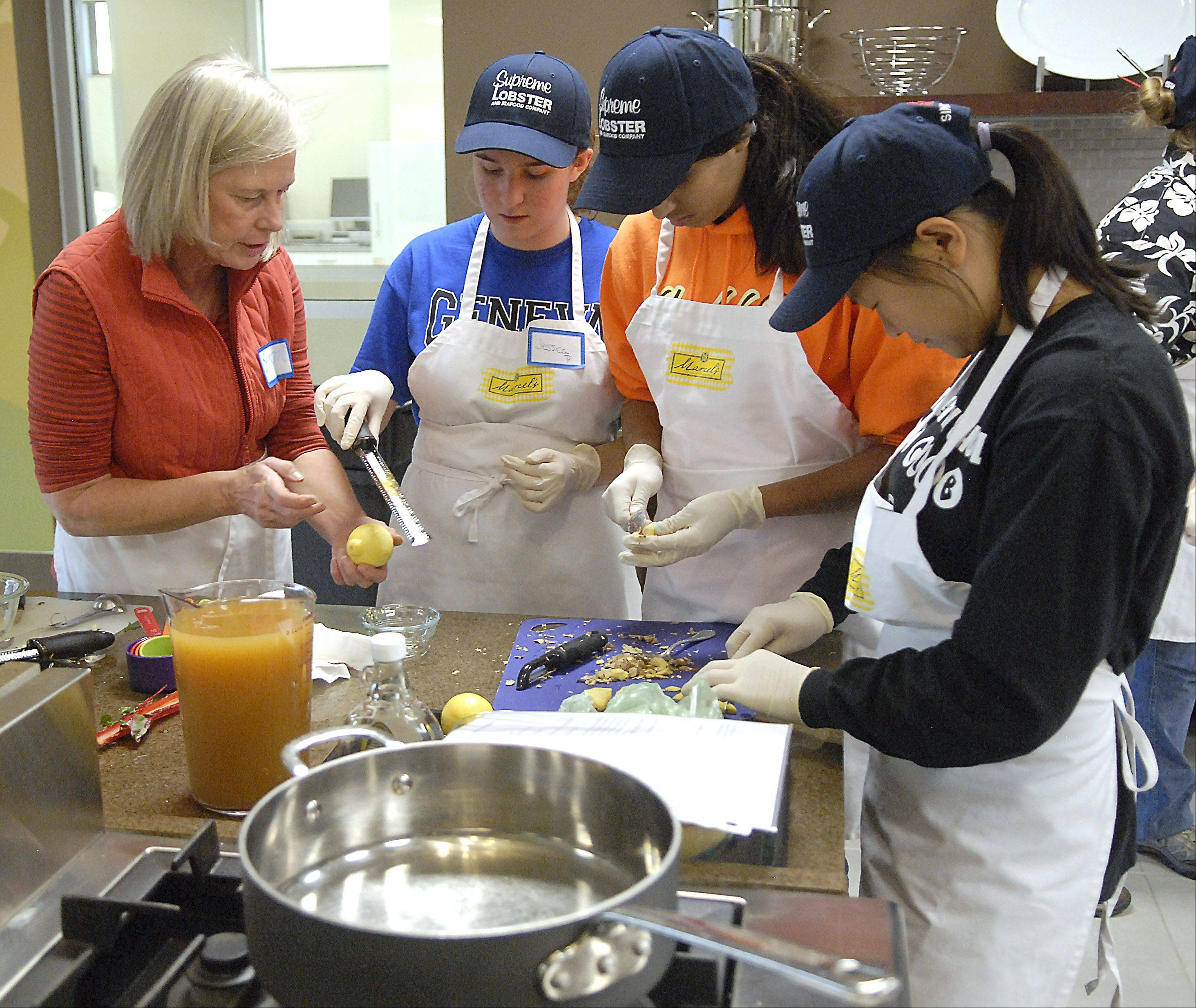 Program director Susan Leigh of Geneva helps Geneva High School students Jessica Prainito, Nila Kannankeril and Anna Green, all 16, while cooking a poached pear dessert at the Roquette kitchen in Geneva. The meals made were for seven cancer patients.