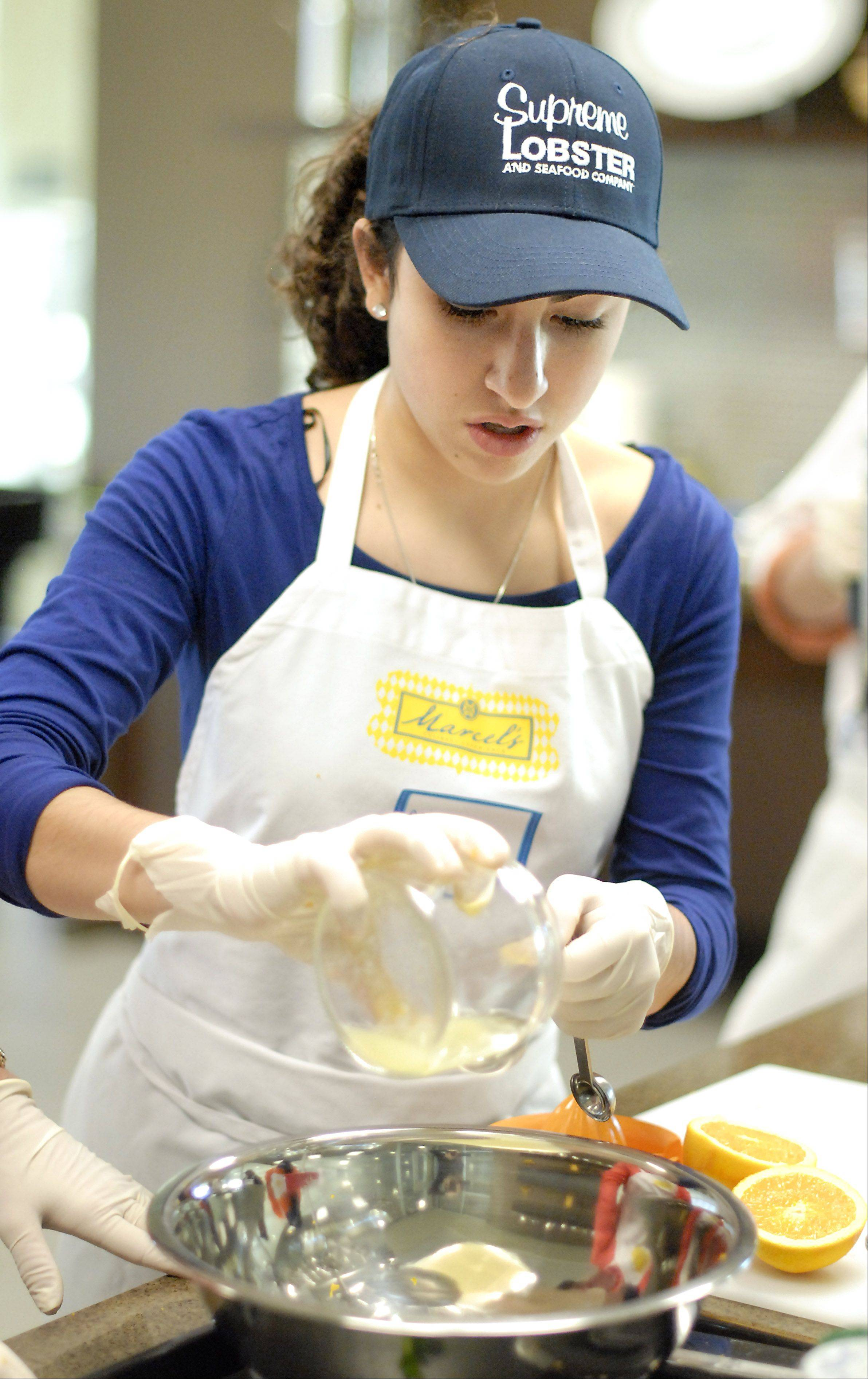 Volunteer Mia Gerace, 14, measures lemon and lime juice for a fish recipe in the Roquette America kitchen in Geneva.