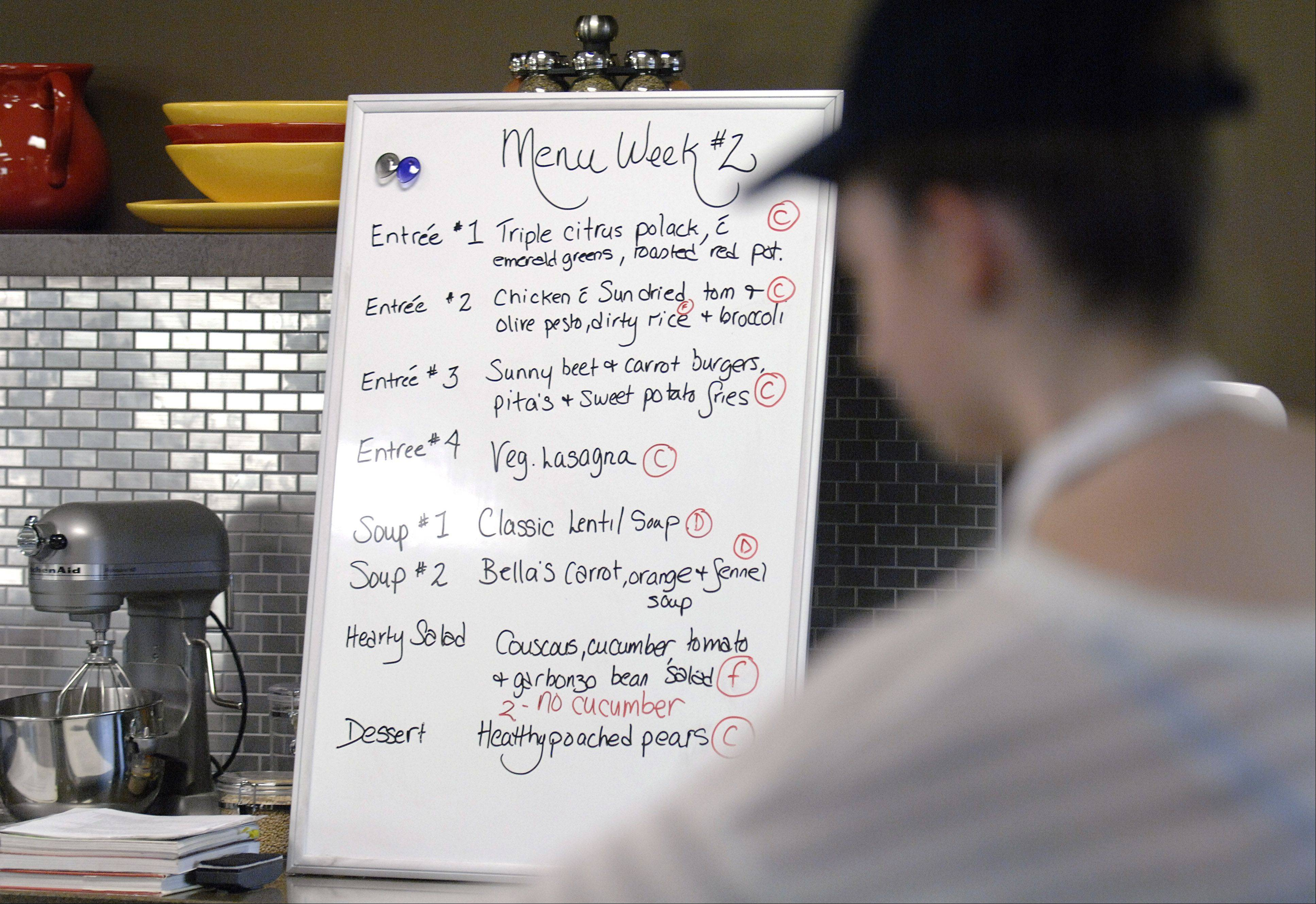 The menu board for this week's meals are on display in the Roquette America kitchen in Geneva, while Lindsay Whitted, 16, works on a dish. Students prepare meals for cancer patients with Fox Valley Food for Health.