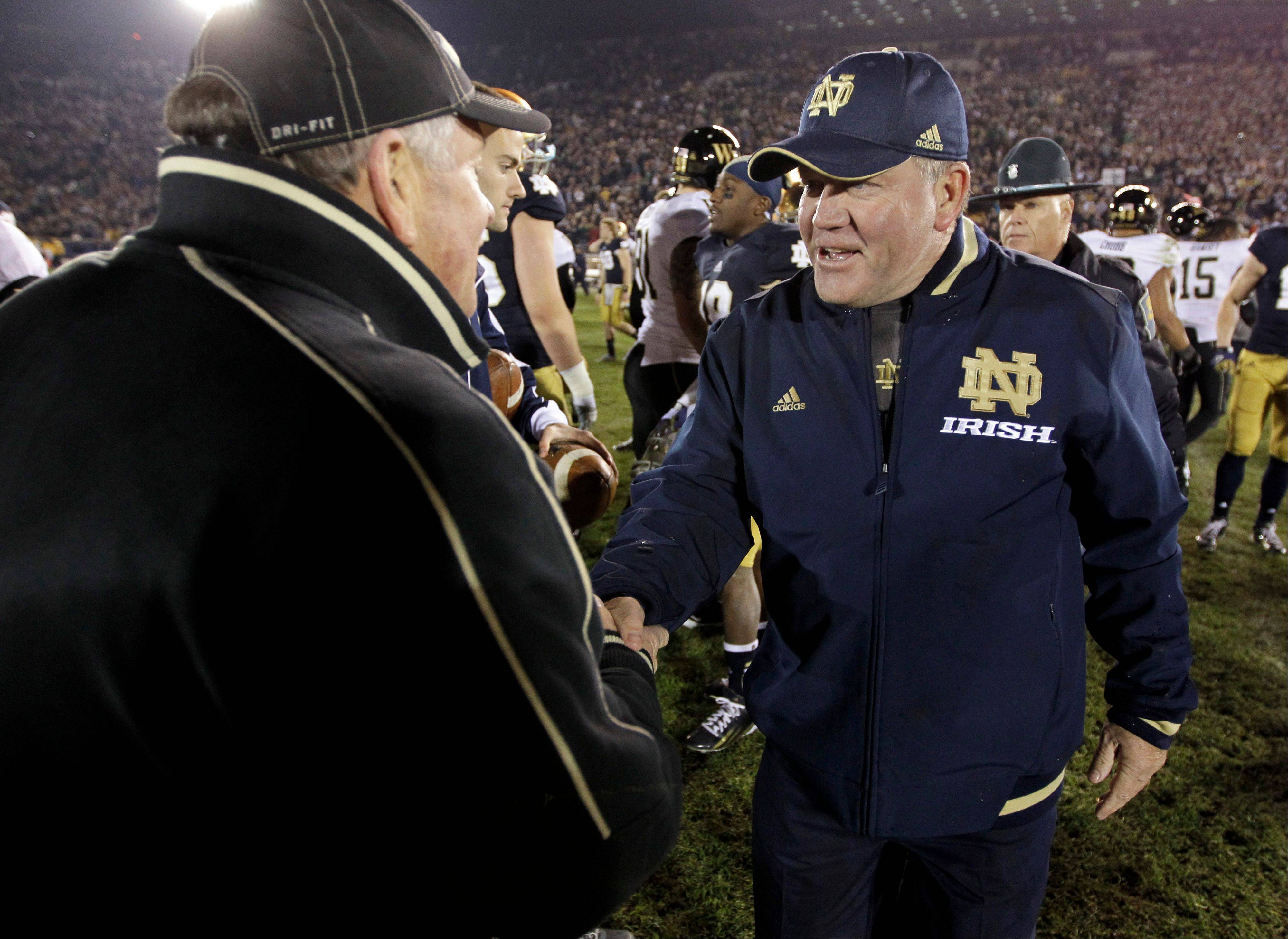 Notre Dame head coach Brian Kelly, right, meets with Wake Forest head coach Jim Grobe following Saturday's 38-0 win by the Fighting Irish.