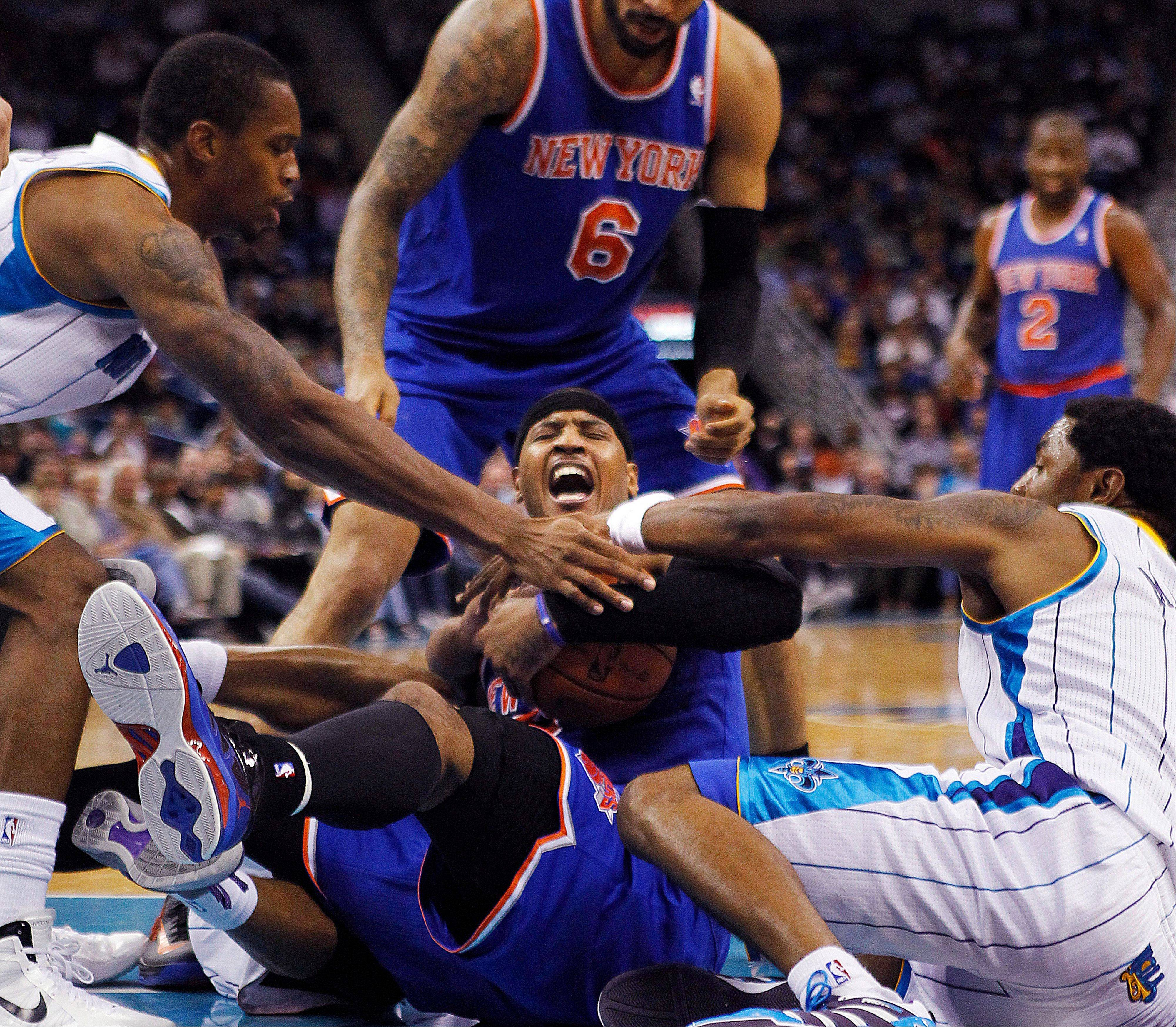 New York Knicks forward Carmelo Anthony, center, wrestles for a loose ball with New Orleans Hornets forward Lance Thomas, left, and guard Roger Mason Jr., right, Tuesday during the first half.