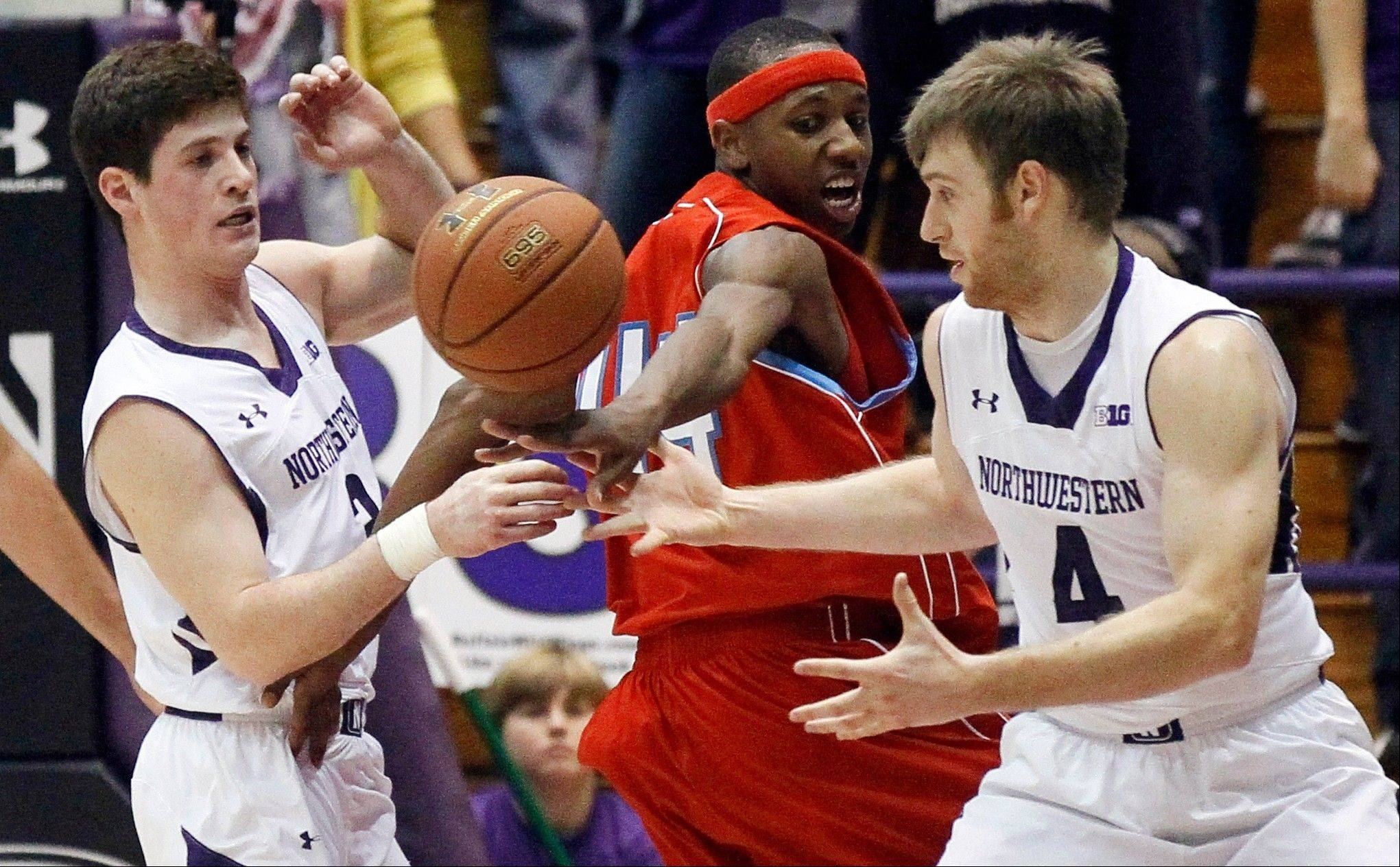 Delaware State guard Amere May loses control of the ball to Northwestern guard Dave Sobolewski (3) and guard Alex Marcotullio Tuesday during the second half in Evanston. Northwestern won 69-50.