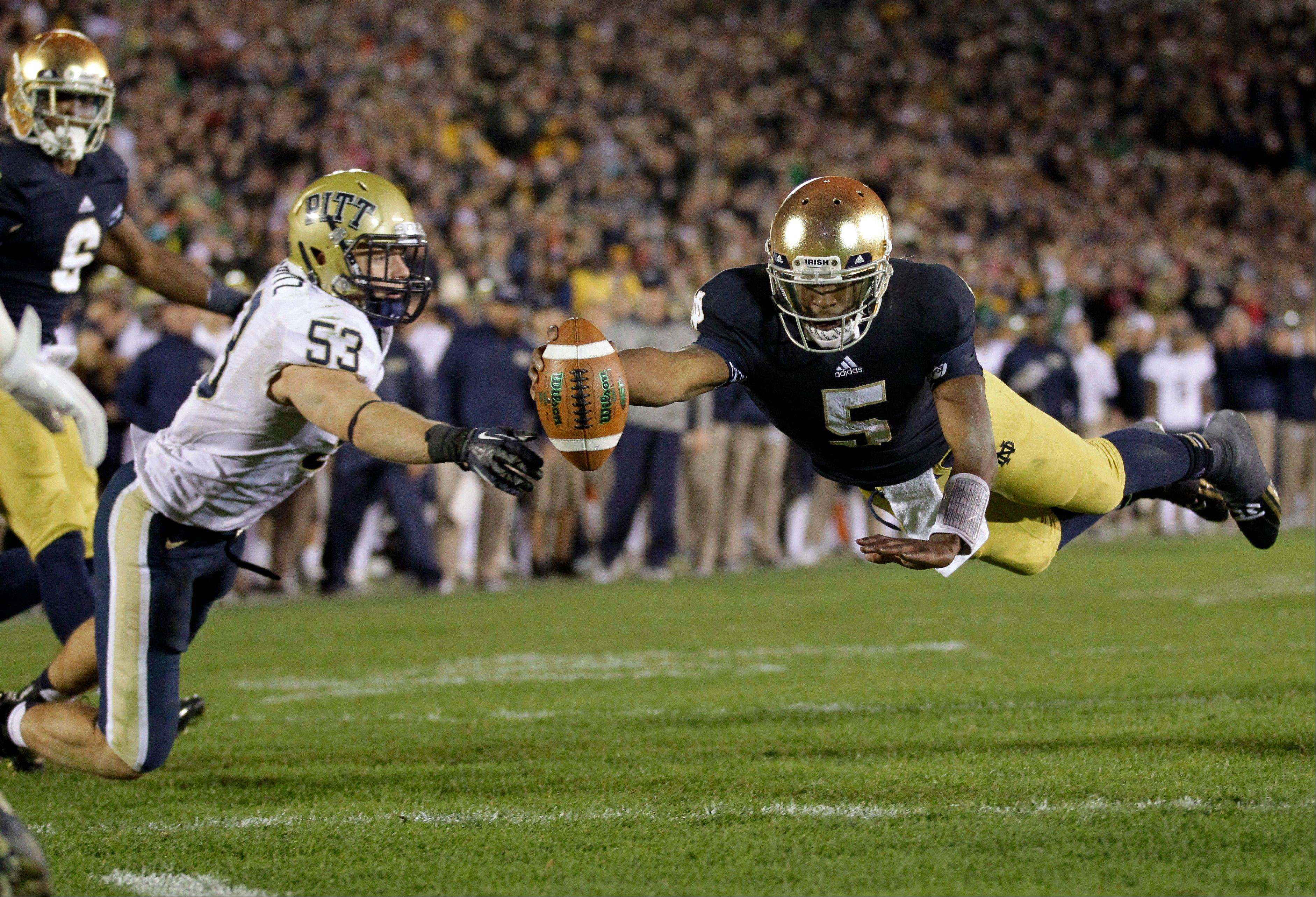 Notre Dame quarterback Everett Golson, right, dives into the end zone in front of Pittsburgh linebacker Joe Trebitz for a two-point conversion to tie the score late in the fourth quarter in South Bend, Ind. Golson is doing a lot more of the little things right, and it's leading to more big plays for top-ranked Notre Dame.