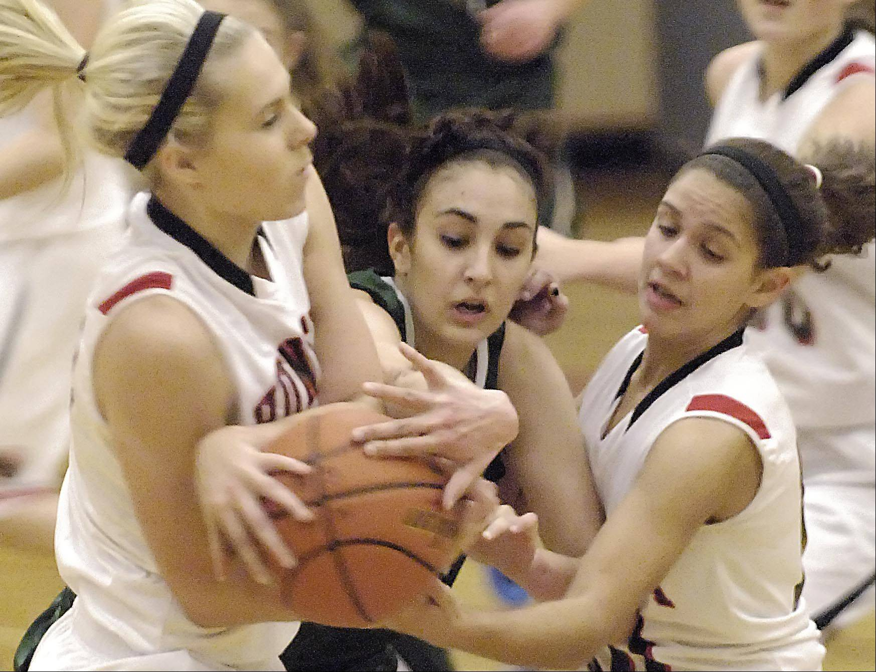 Bartlett's Elizabeth Arco has the ball stripped away by Huntley's Ali Andrews left, and Kayla Barreto Tuesday in Huntley.