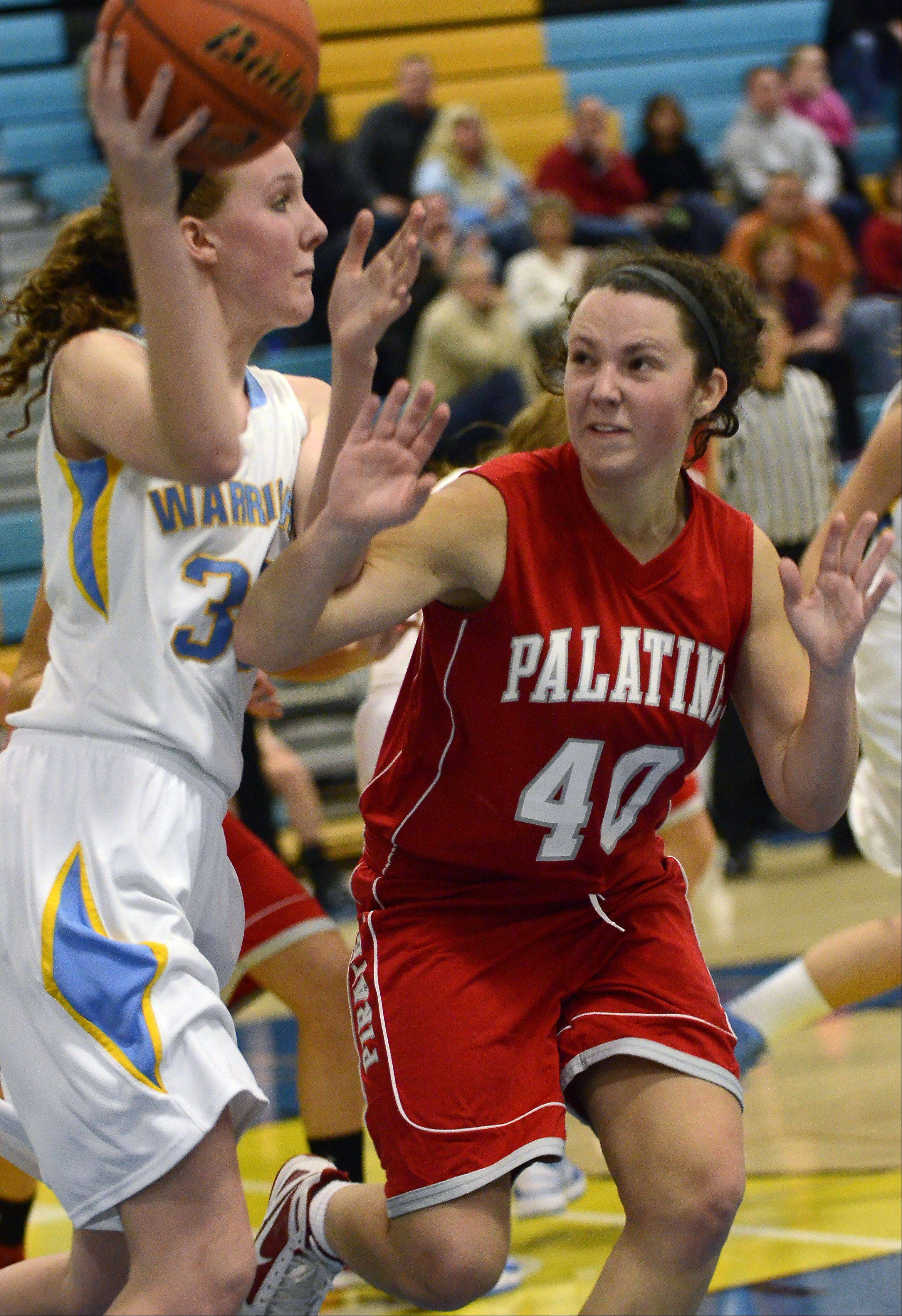 Maine West's Brittany Collins, 30, passes around Palatine's Jamie Lloyd during the season basketball opener Monday.