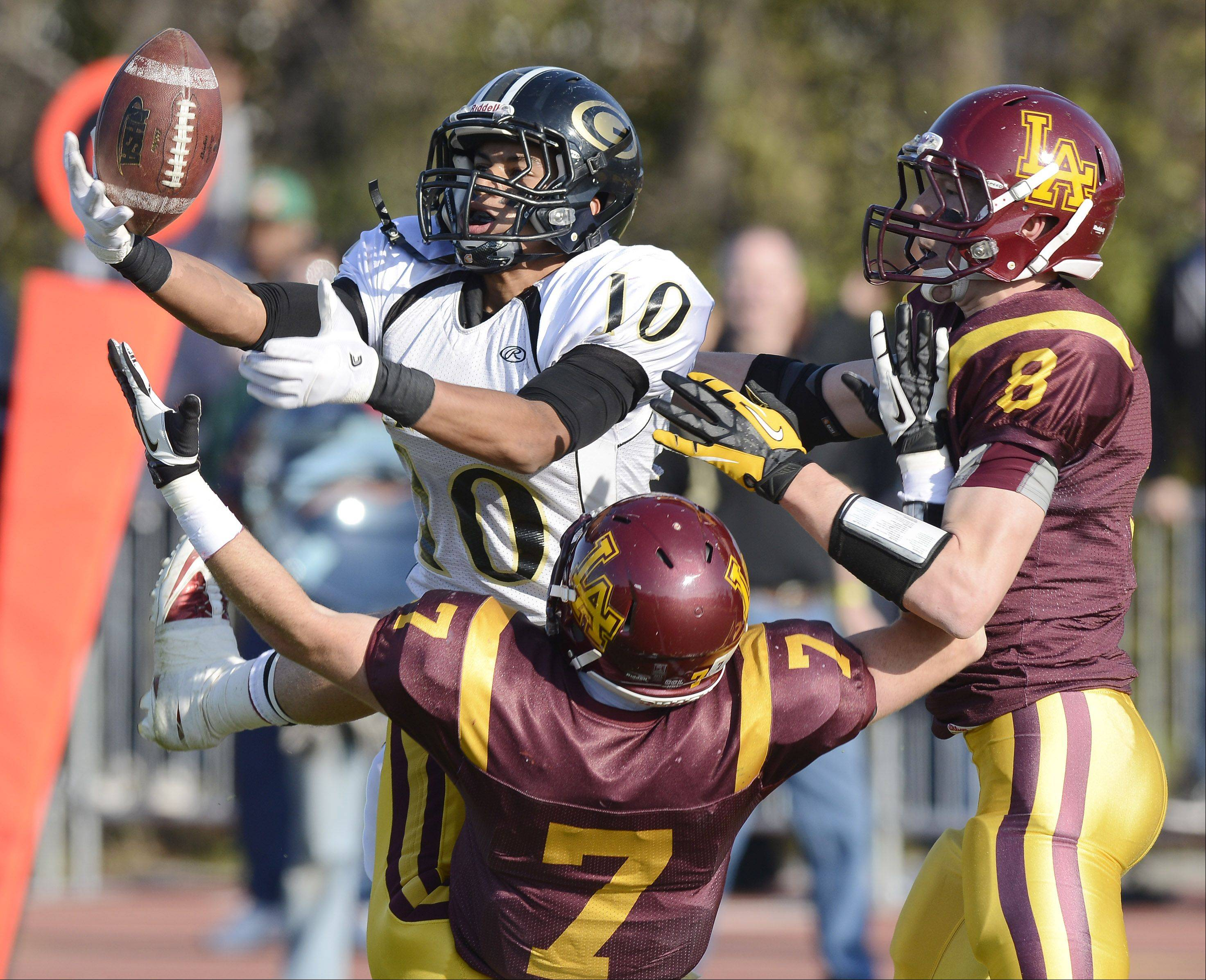 Glenbard North's Kendall Holbert can't hang onto a pass while being covered by Loyola Academy's Daniel Rafferty, front, and Luke Ford, right, during Saturday's class 8A football playoff semifinal.