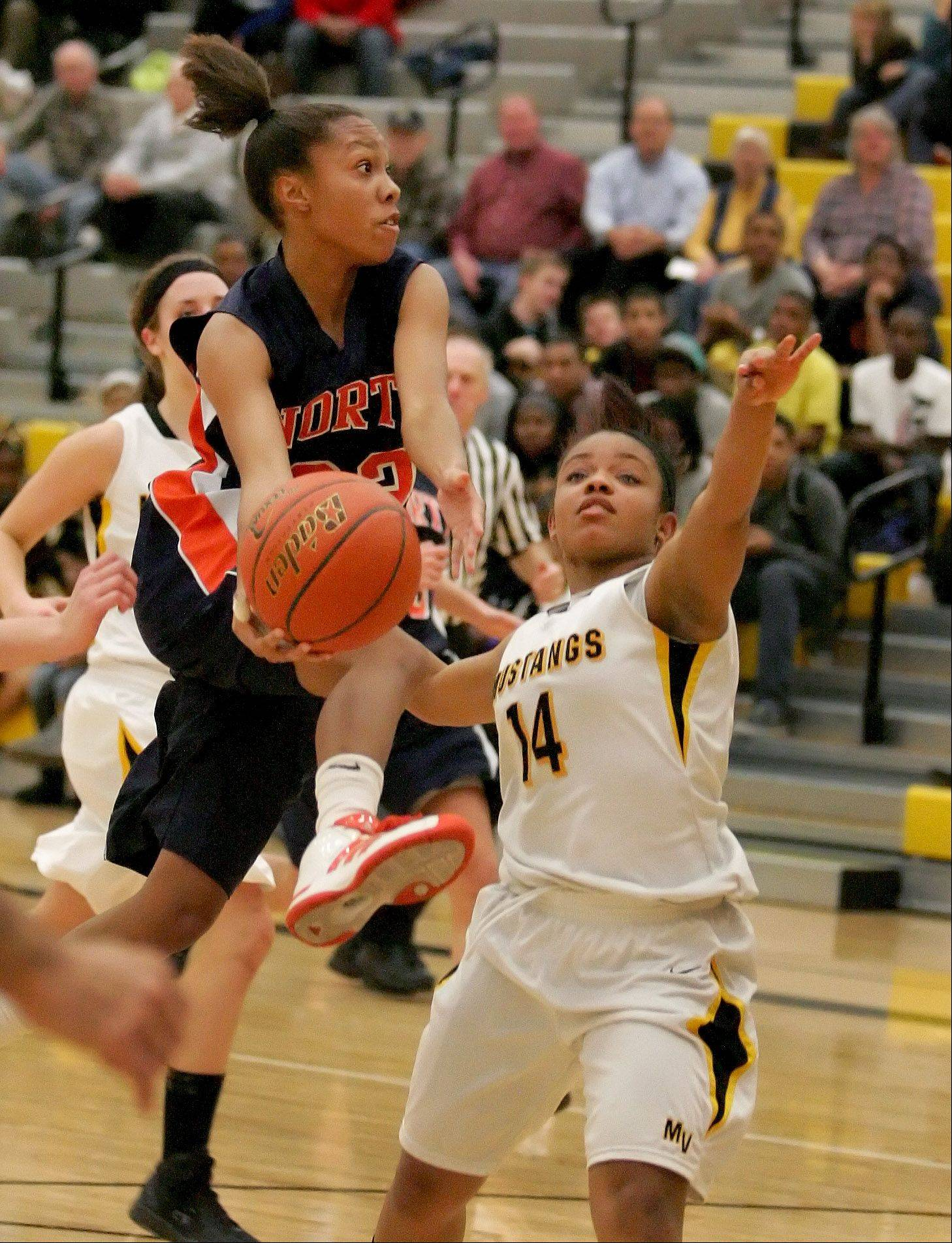 Naperville North's Zoe Swift, left, heads to the basket past Metea Valley's Kellee Clay Tuesday in Aurora.
