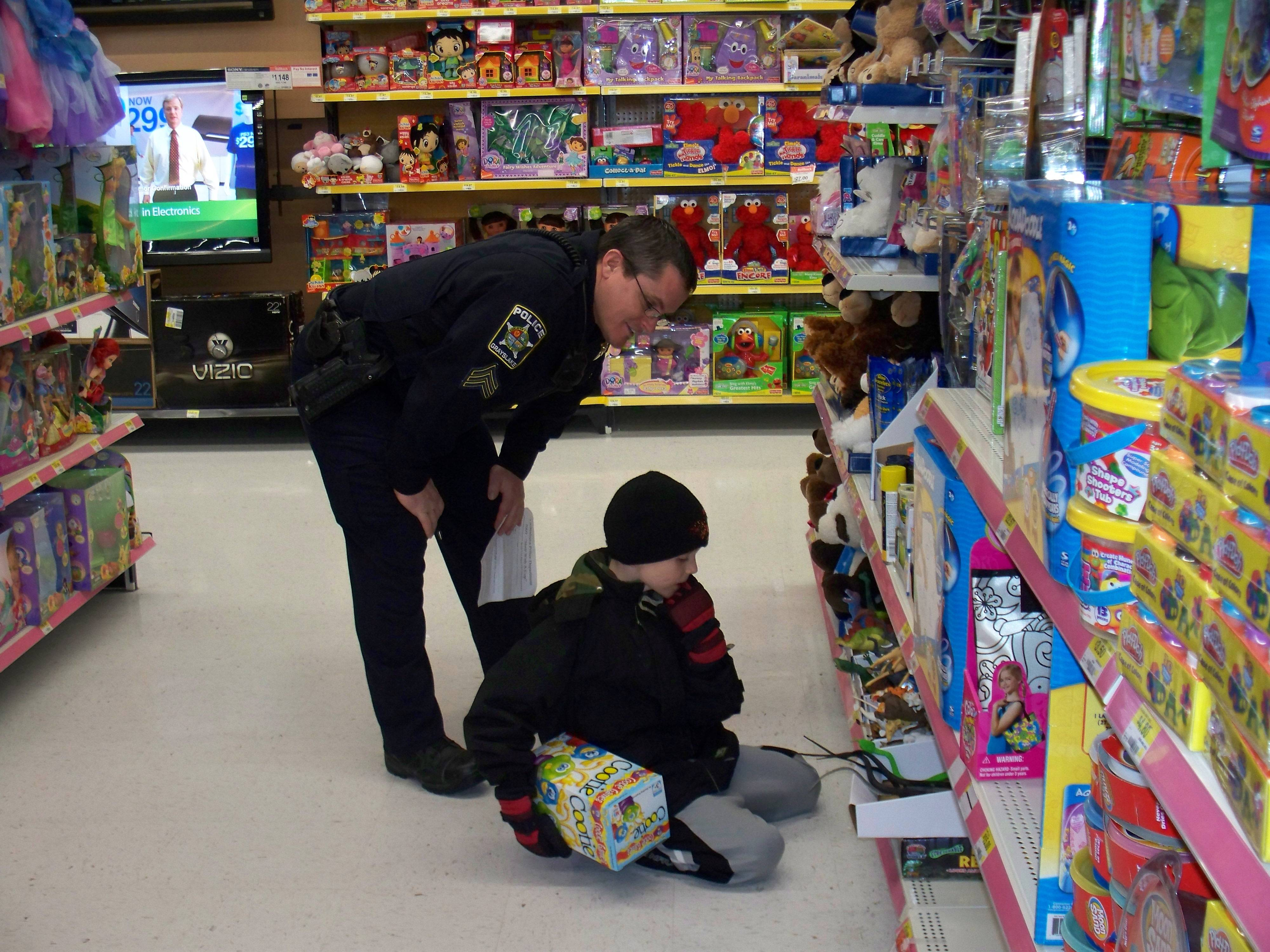 Officer Foy helps a child contemplate a purchase.