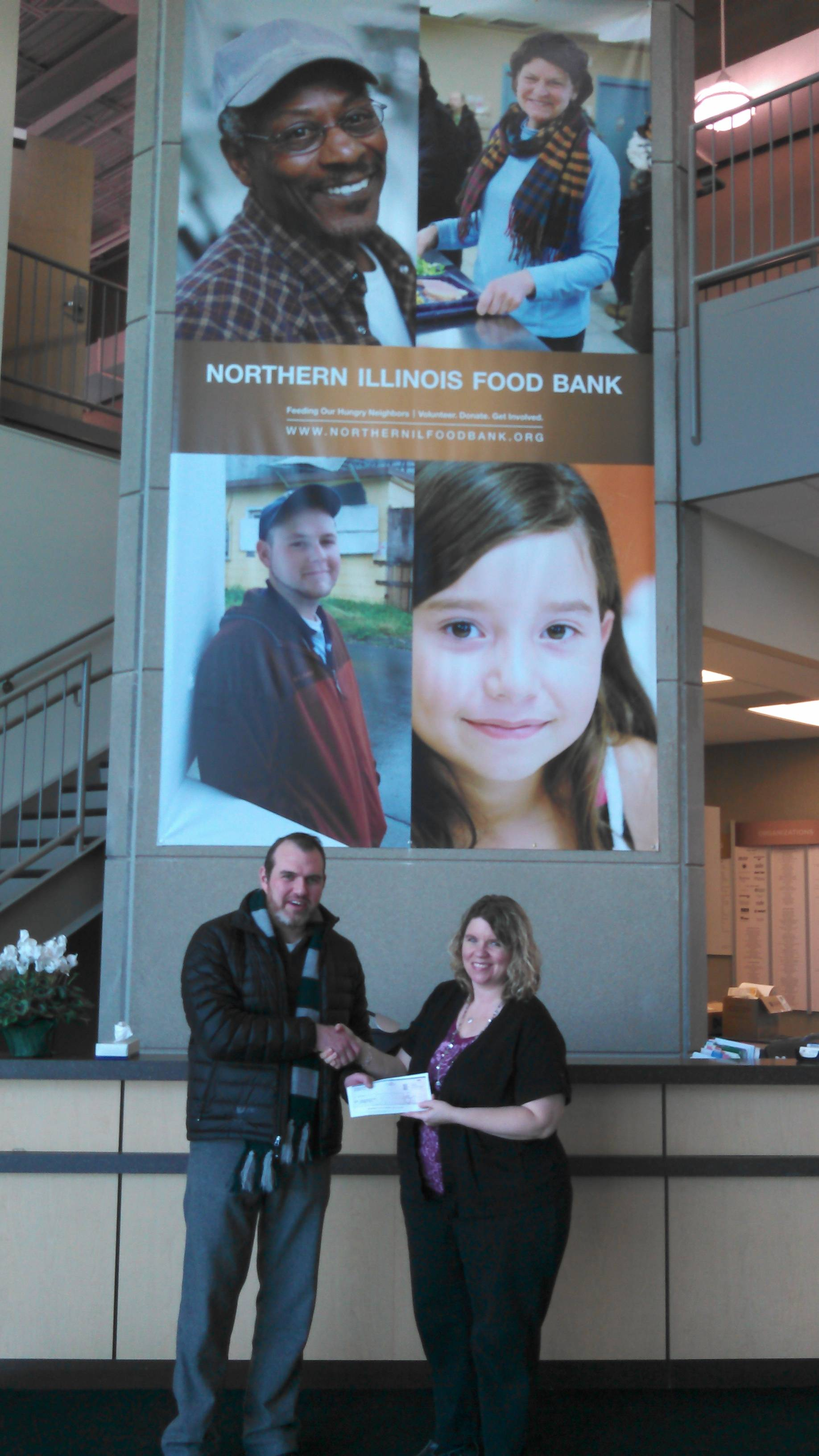 Fox Valley Rep Artistic Director John Gawlik presents Shannon Thompson of Northern Illinois Food Bank with a check for $1,000.