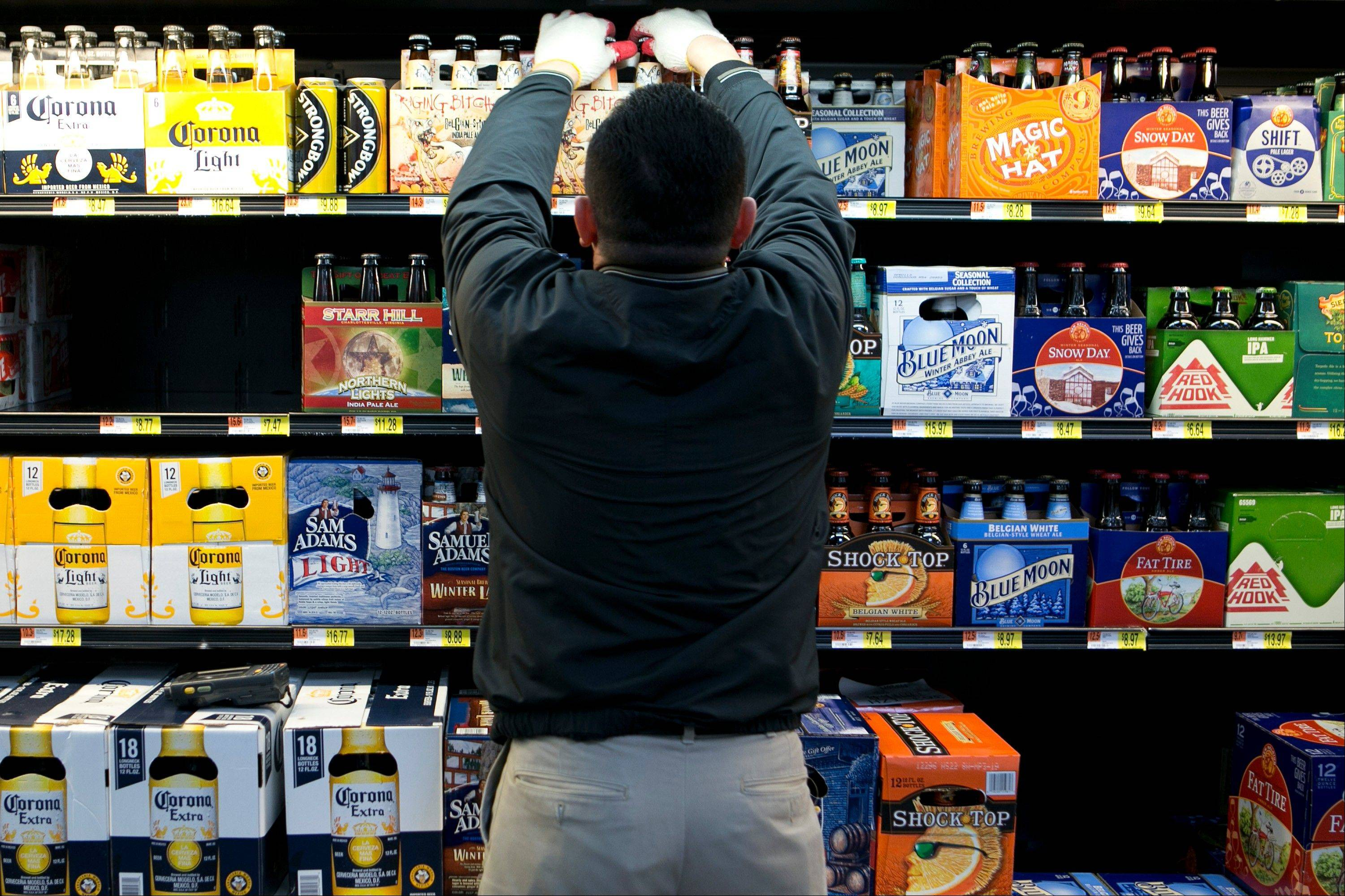 Miguel Bustillo stocks the beer cooler at a Wal-Mart store in Alexandria, Virginia, U.S.