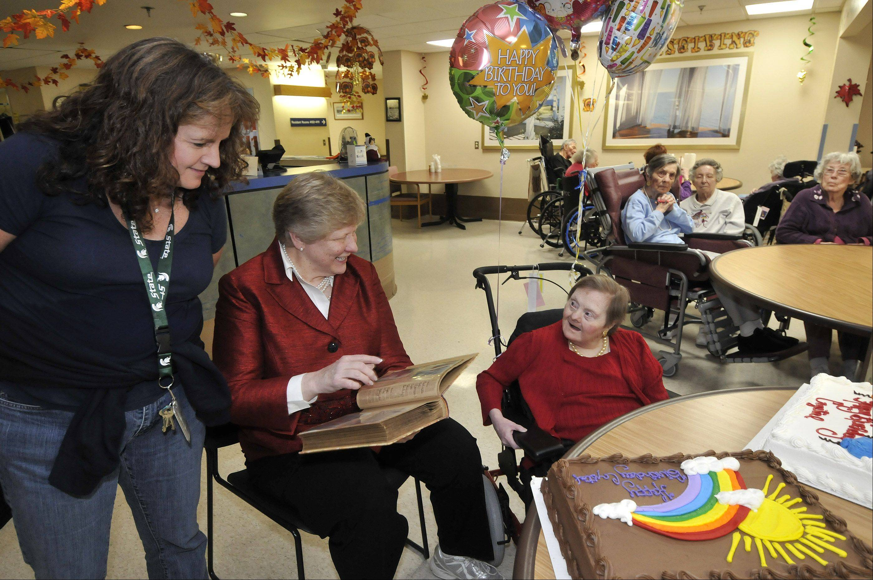 Crystal Barton, right, who lives at the DuPage Convalescent Center in Wheaton, recently turned 71. Her half-sister, Barbara Doerschuk, center, was on hand to show photos of Crystal to her and friends at the center. Susan Coblentz, a manager of recreation therapy at the center, organized the birthday party.