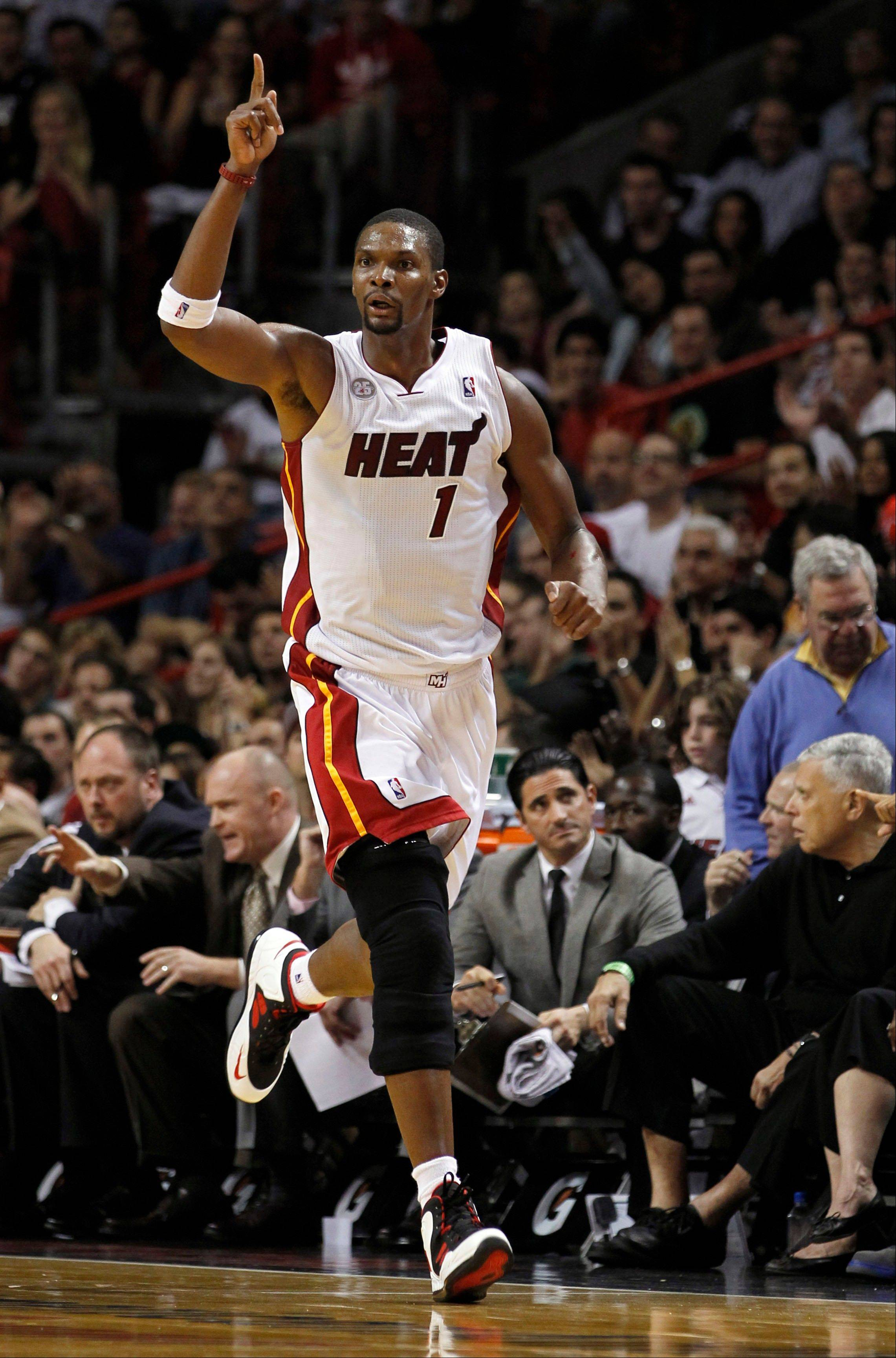Miami�s Chris Bosh celebrates after scoring a 3-pointer in the second half Wednesday at home against the Milwaukee Bucks. Bosh scored 28 points and had 18 rebounds, his most in a Heat uniform.