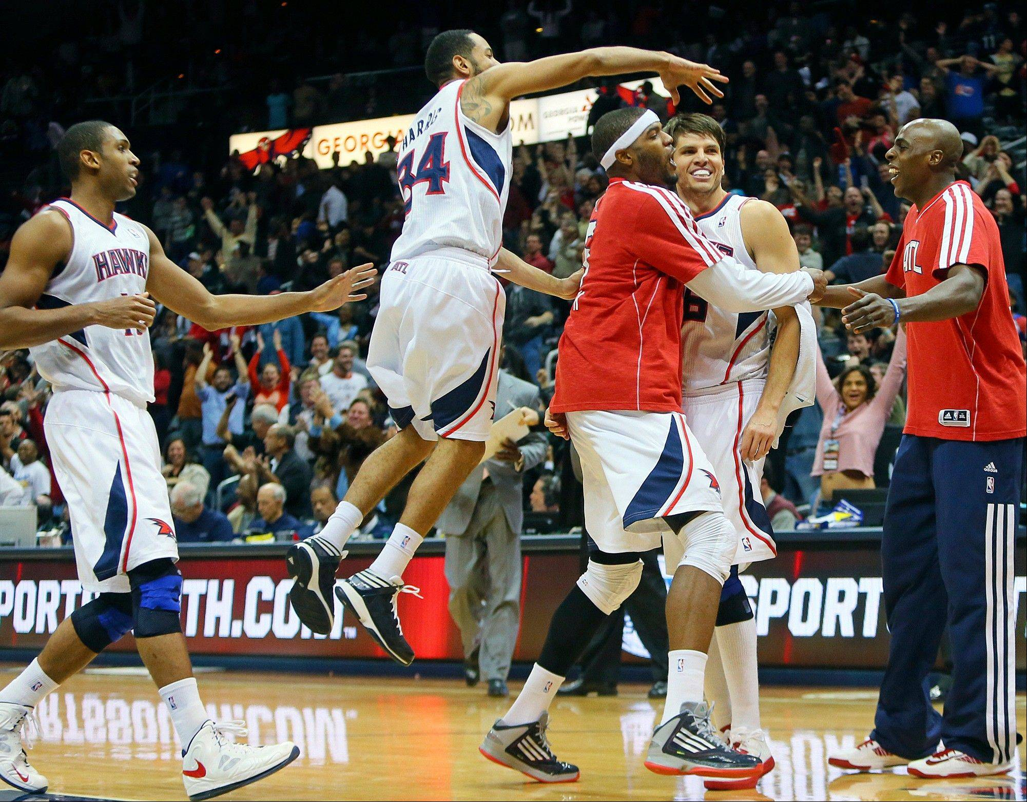 The Hawks� Josh Smith, third from right, grabs Kyle Korver, second from right, after Korver hit the winning 3-pointer against the Washington Wizards on Wednesday in Atlanta.