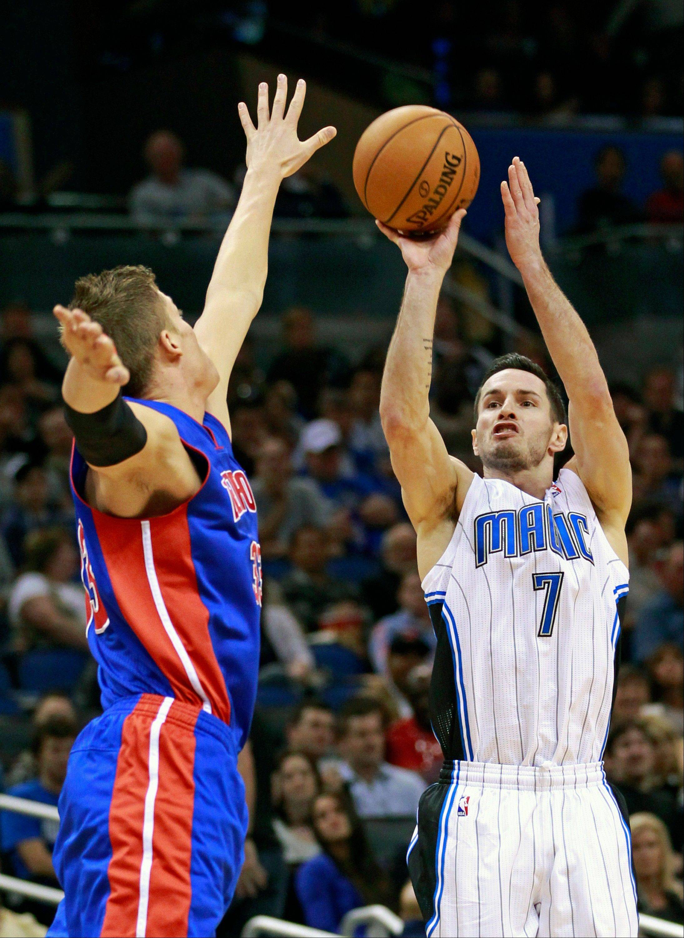 The Magic�s J.J. Redick takes a 3-point shot over the arms of Detroit�s Jonas Jerebko during the second half Wednesday in Orlando.