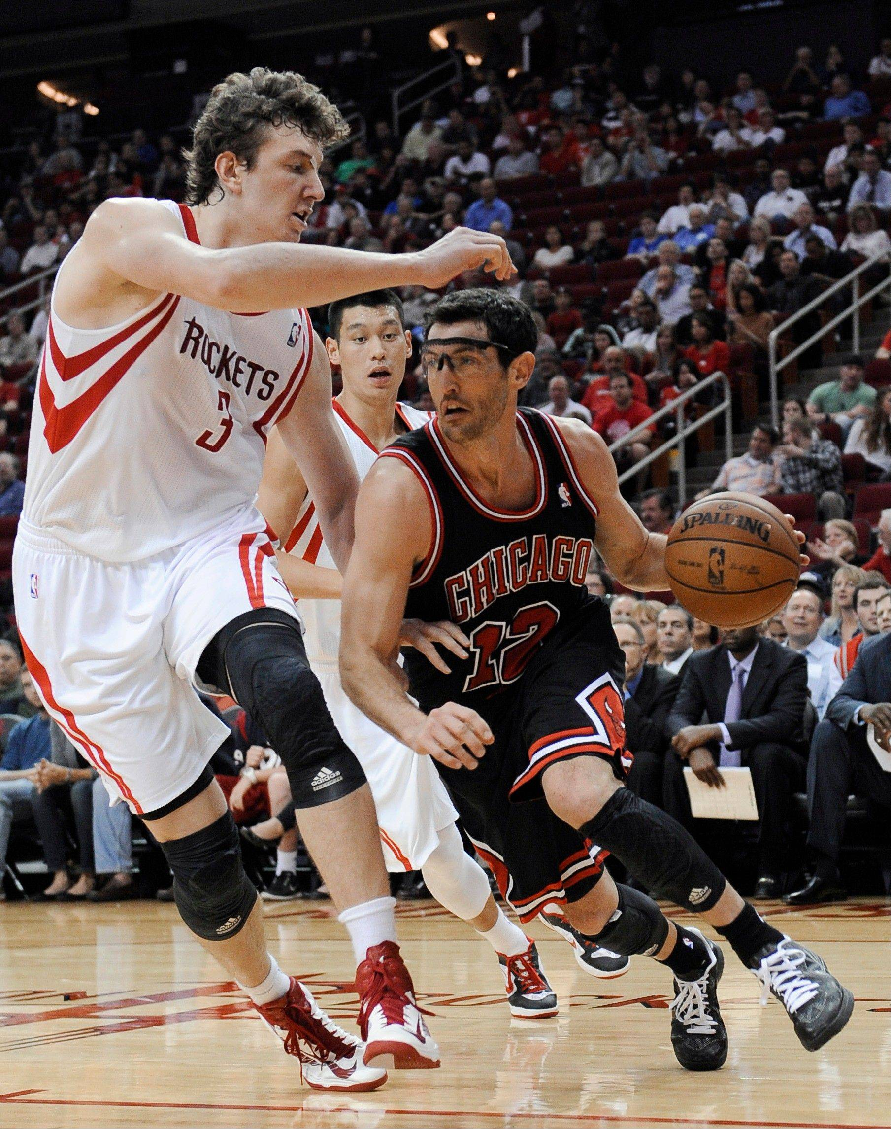 The Bulls� Kirk Hinrich drives around the Rockets� Omer Asik (3) as Jeremy Lin watches from behind in the first half Wednesday in Houston.