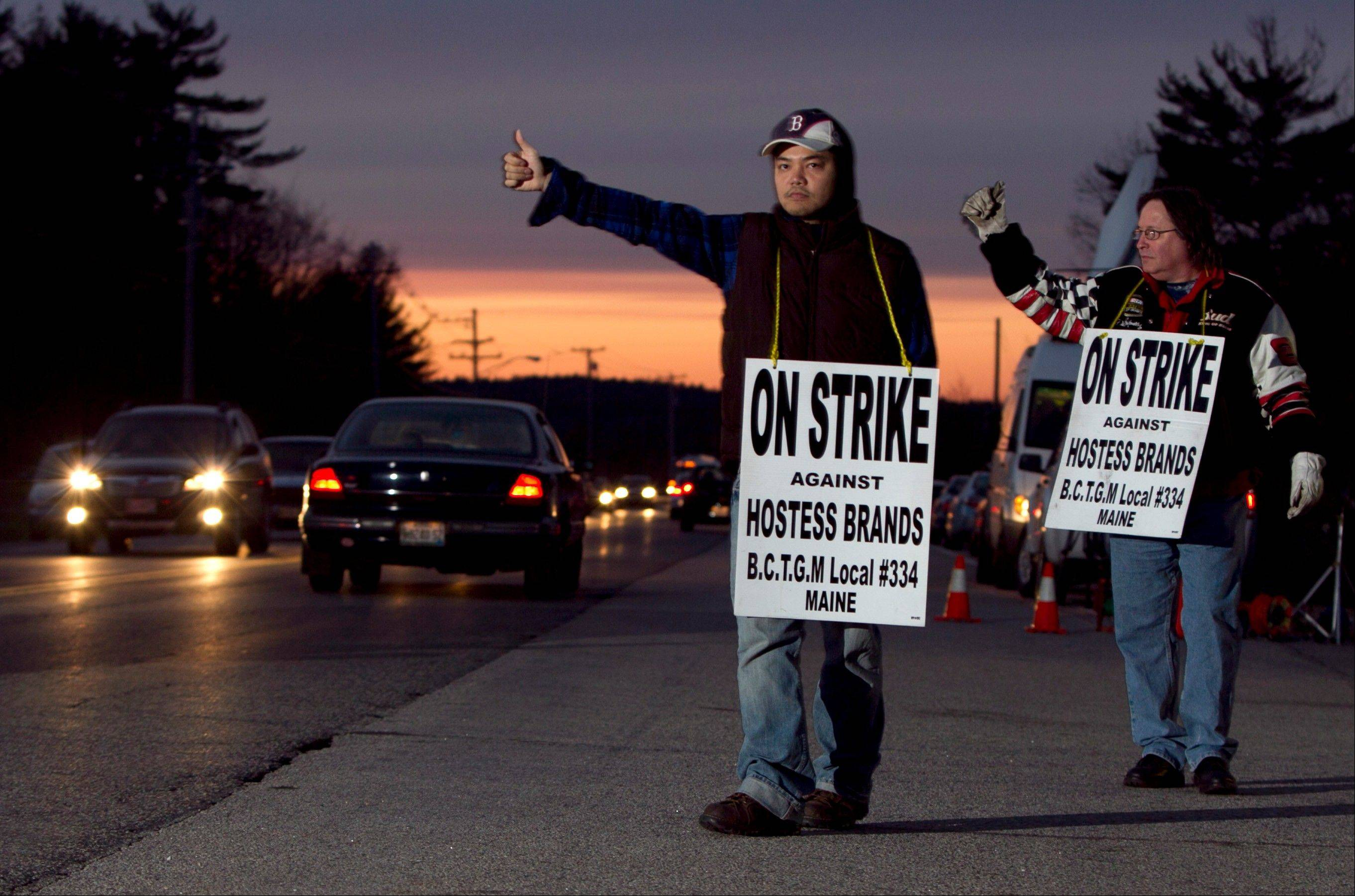 Striking workers Nam Phan, left, and Randy Goodwin picket outside a Hostess Brand plant, Friday in Biddeford, Maine.