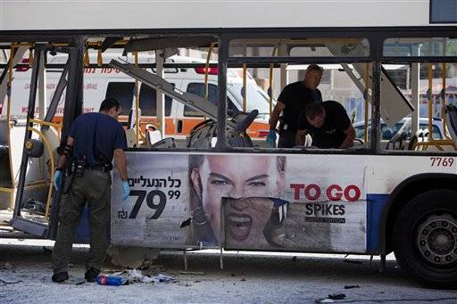 Israeli police officers examine a blown up bus at the site of a bombing in Tel Aviv, Israel, Wednesday.