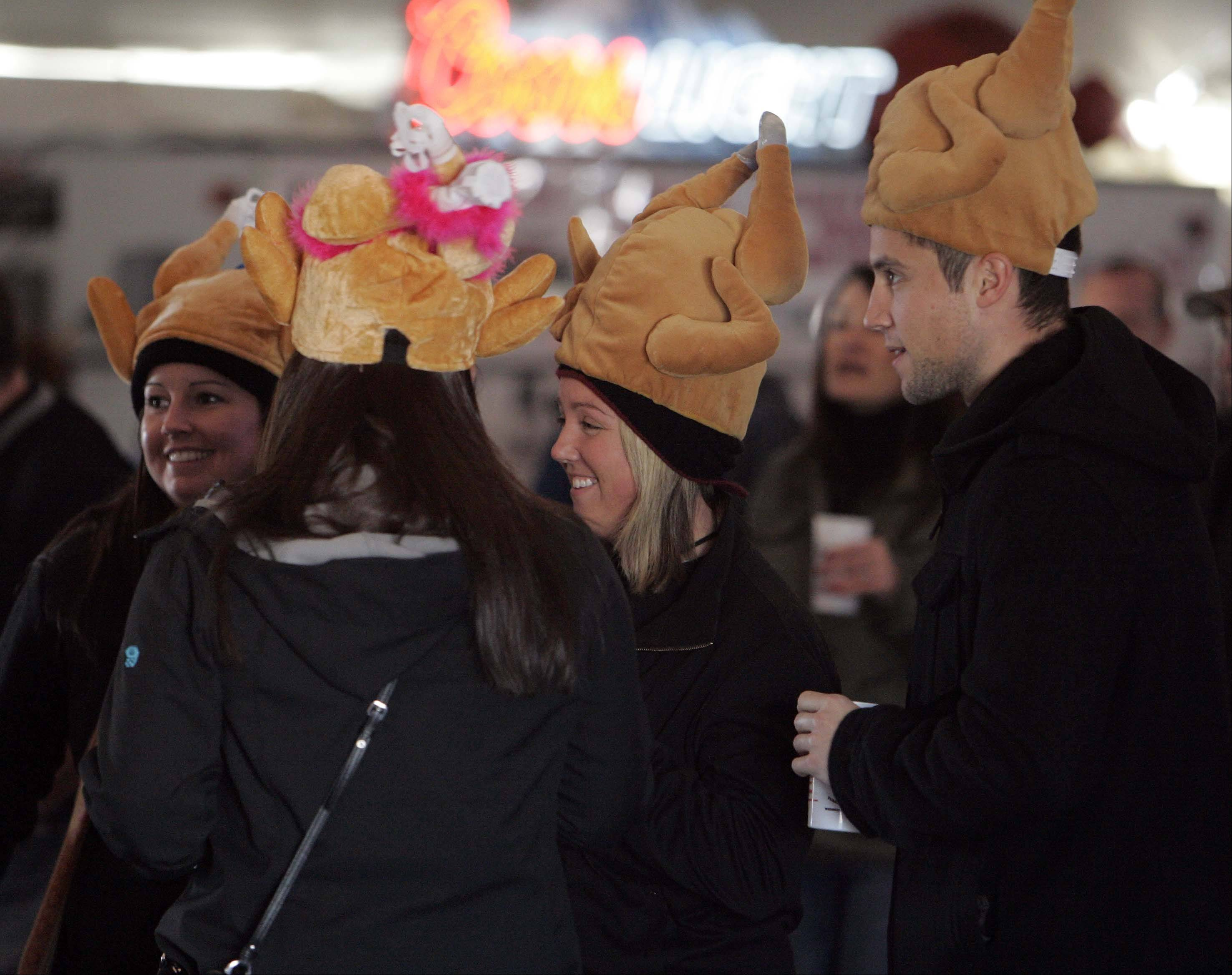 Kelsey Malmstead of St. Charles, from left, Amy Malmstead of Moline, (back to camera) Sara Haddox and her brother Patrick Haddox both of St. Charles, don turkey hats while enjoying a drink at the Turkey Testicle Festival in Huntley. Parkside Pub workers will fried up about 1,200 pounds of testicles this year during the pub's 30th annual festival. The organizers are hoping for 4,500 guests this year, which would beat an attendance record set in 2011.