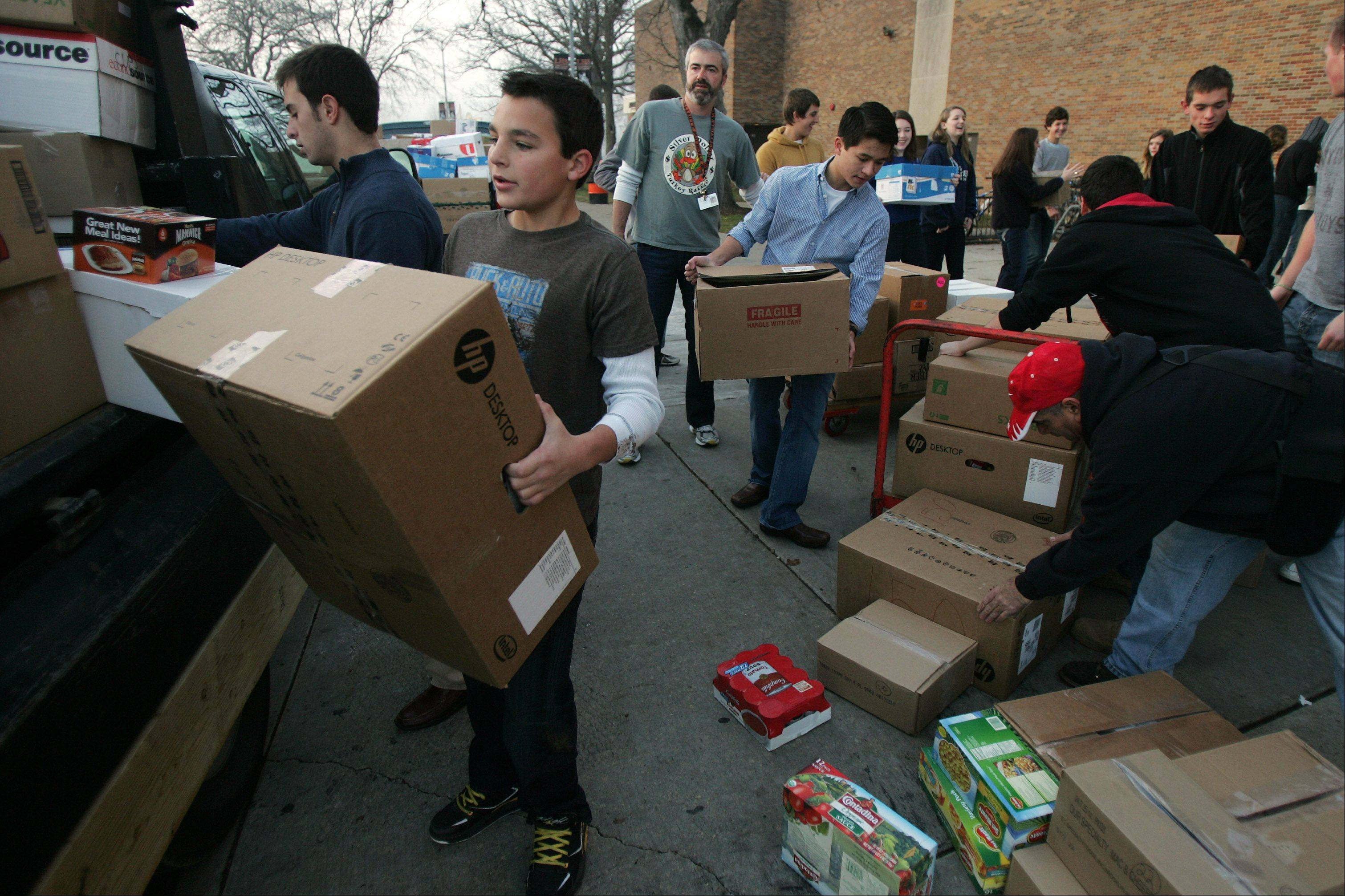 Libertyville High School freshman Nick Kraus, left, joins other students and teachers to pack up boxes of donated food Wednesday. Students collected more than 10,000 items to donate to the Libertyville Township food pantry.