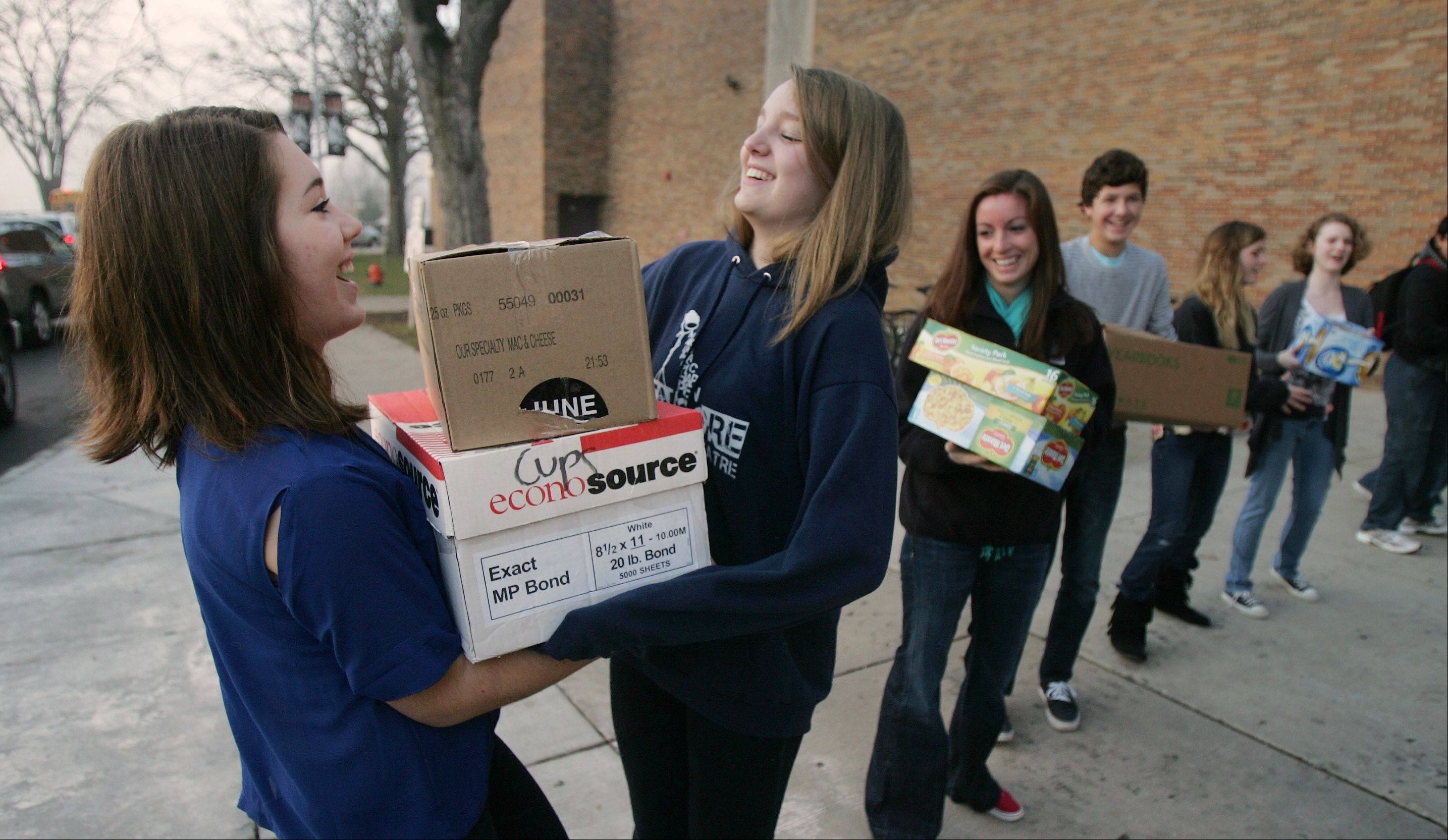 Libertyville High School sophomore Madison Basich receives a box from freshman Taylor Skie on Wednesday as students form a human chain to load up trucks with items being donated to the Libertyville Township food pantry.