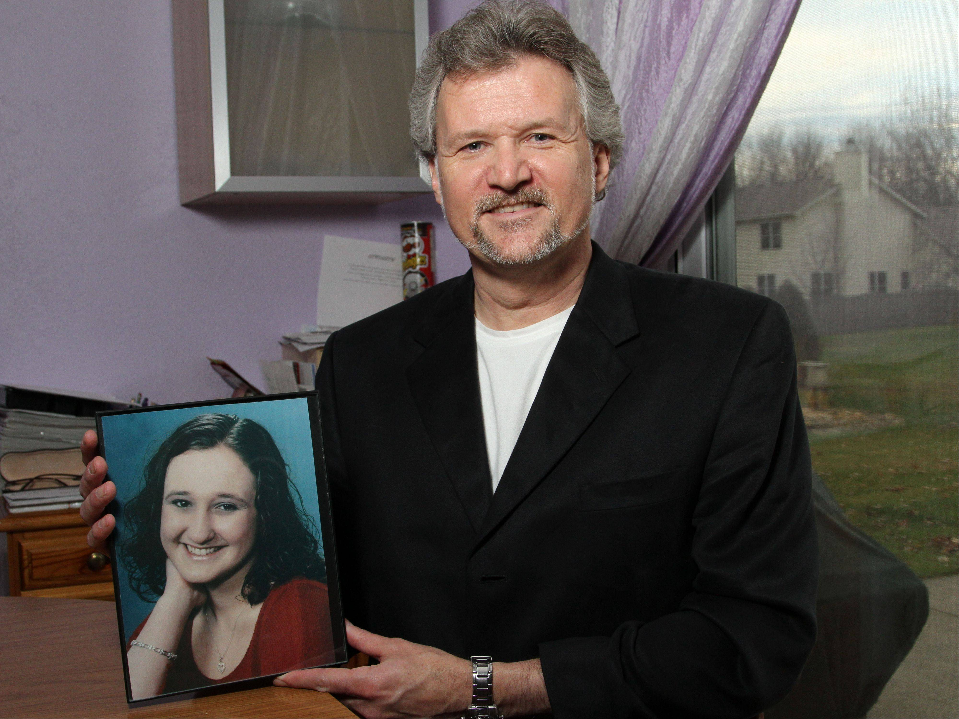 Gurnee resident Jim Stanislawski holds a picture of his late daughter Jackie, who was killed in a 2003 auto accident. For the last eight years Stanislawski has staged annual magic shows that double as food drives in honor his late daughter.