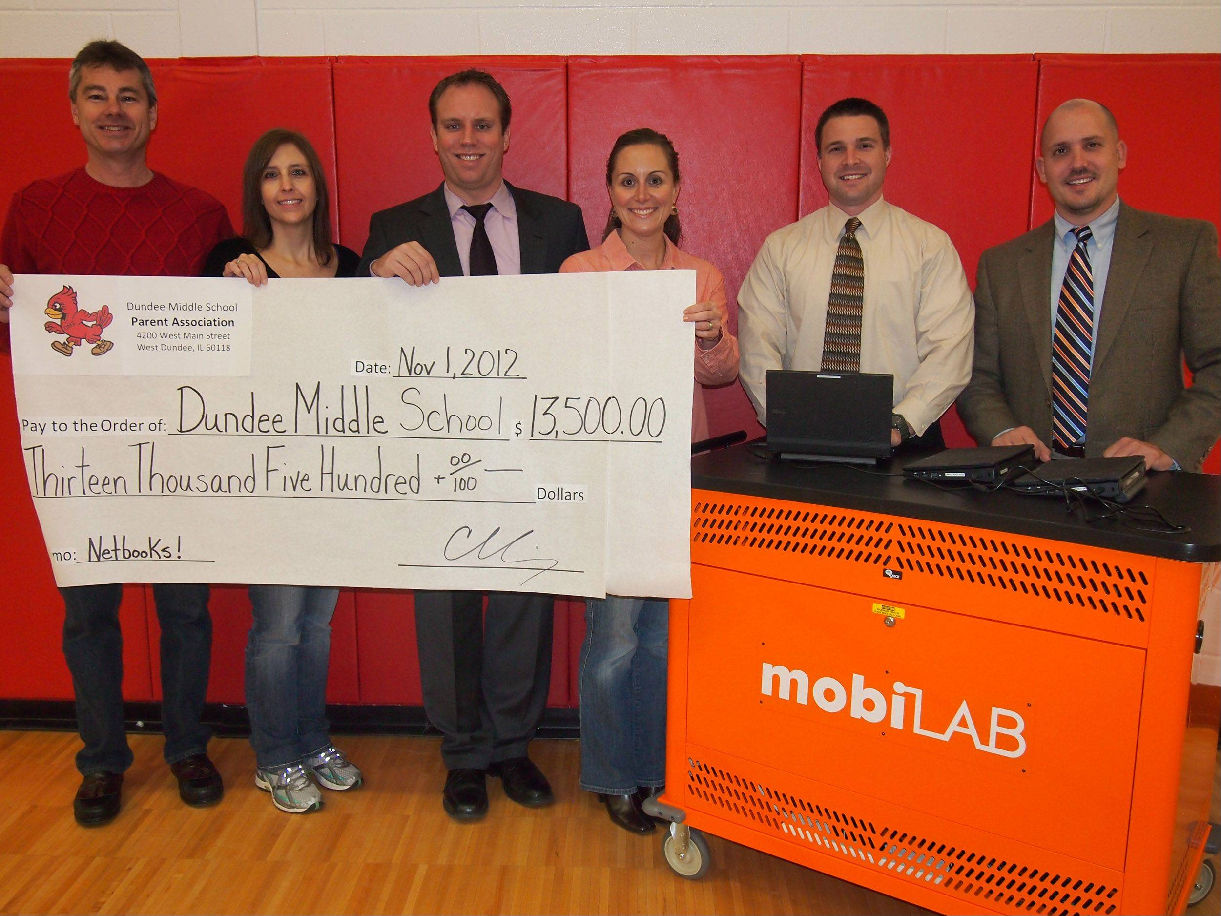 Dundee Middle School administrators and parent association members, from left, Gary Andersen, president; Ann Girten, treasurer; Joe Schumacher, principal; Carrie Koenig, vice president; Andy Reinke, assistant principal and Chris Testone, assistant principal, show off a check for $13,500 and a mobile netbook cart.