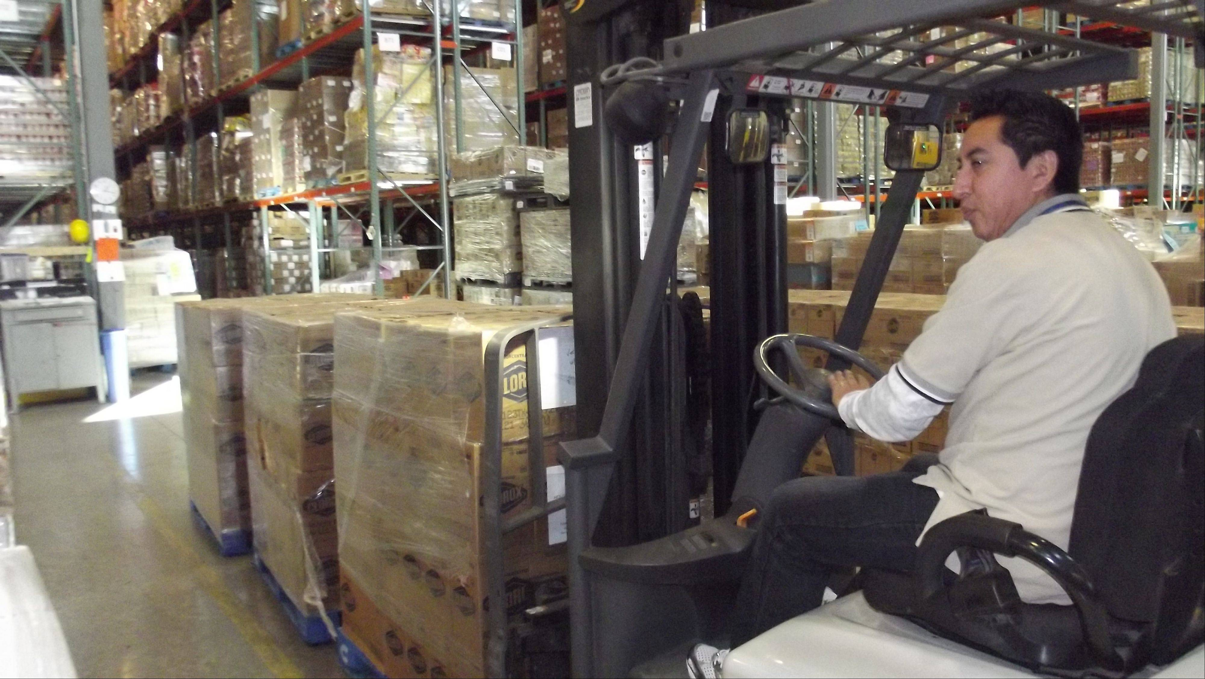 Genaro Elizalde, warehouse manager of the Northern Illinois Food Bank in St. Charles, preps the donation of a truckload of bleach to Island Harvest Food Bank in New York for delivery.
