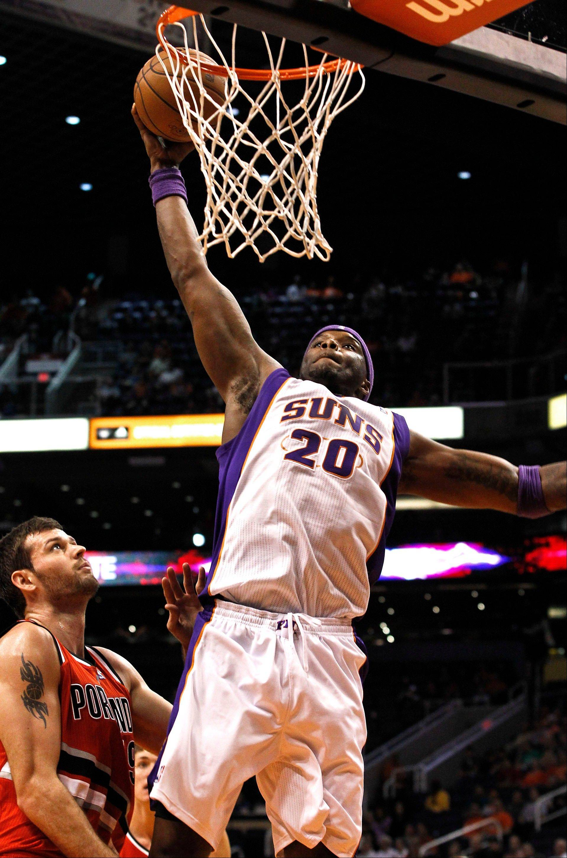 The Suns' Jermaine O'Neal (20) goes in for a dunk as Portland's Joel Freeland watches during the second half Wednesday in Phoenix.