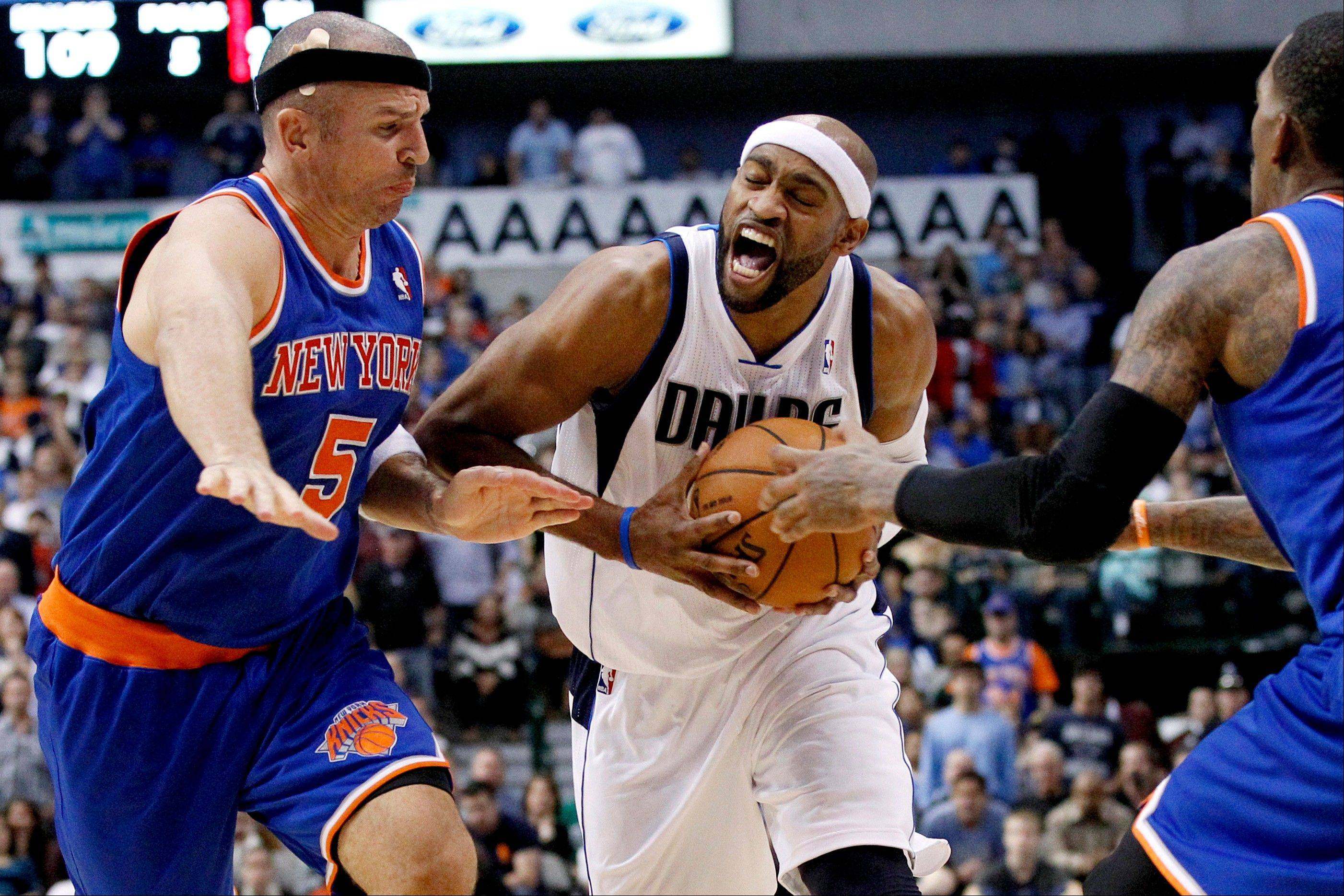 New York's Jason Kidd (5) and J.R. Smith (8) defend as the Mavericks' Vince Carter (25) attempts a drive to the basket in the second half Wednesday in Dallas. The Mavericks won 114-111.