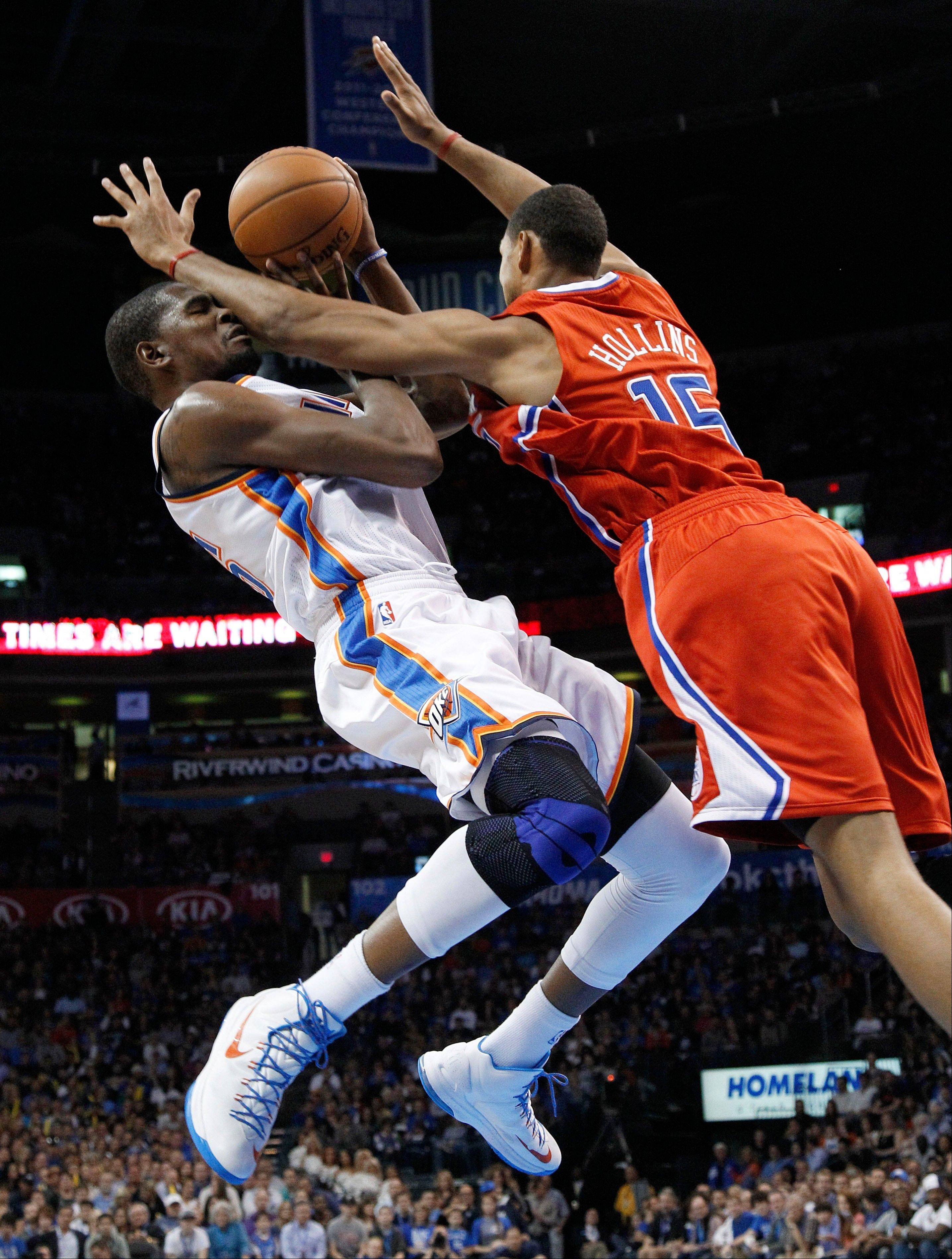 Oklahoma City Thunder forward Kevin Durant (35) is fouled by Los Angeles Clippers center Ryan Hollins (15) as he shoots in the third quarter Wednesday at home.
