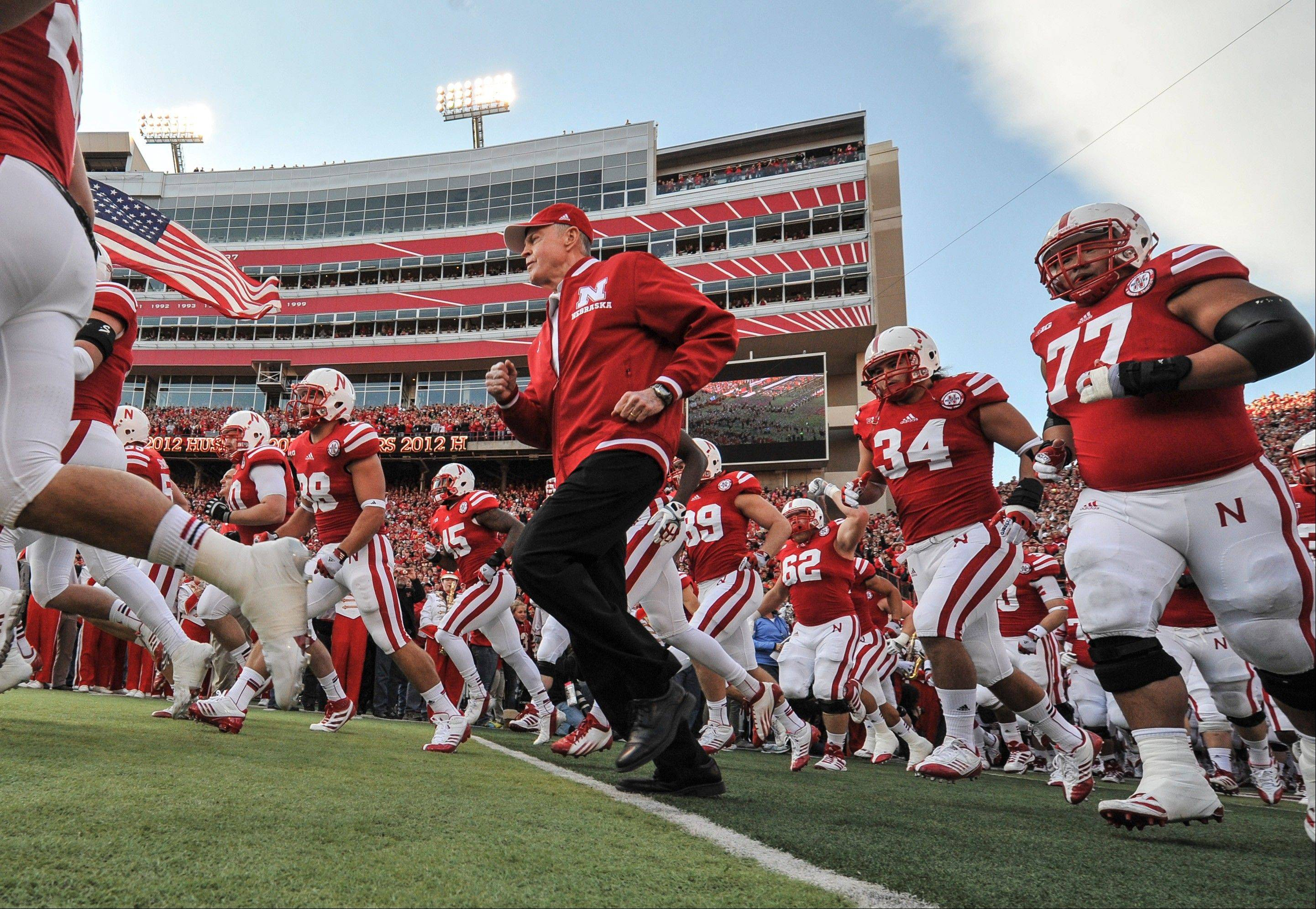 Nebraska's retiring athletic director and former coach Tom Osborne runs onto the field with players prior to Saturday's game against Minnesota, in Lincoln, Neb. Osborne was honored for his involvement in 500 Nebraska football games.