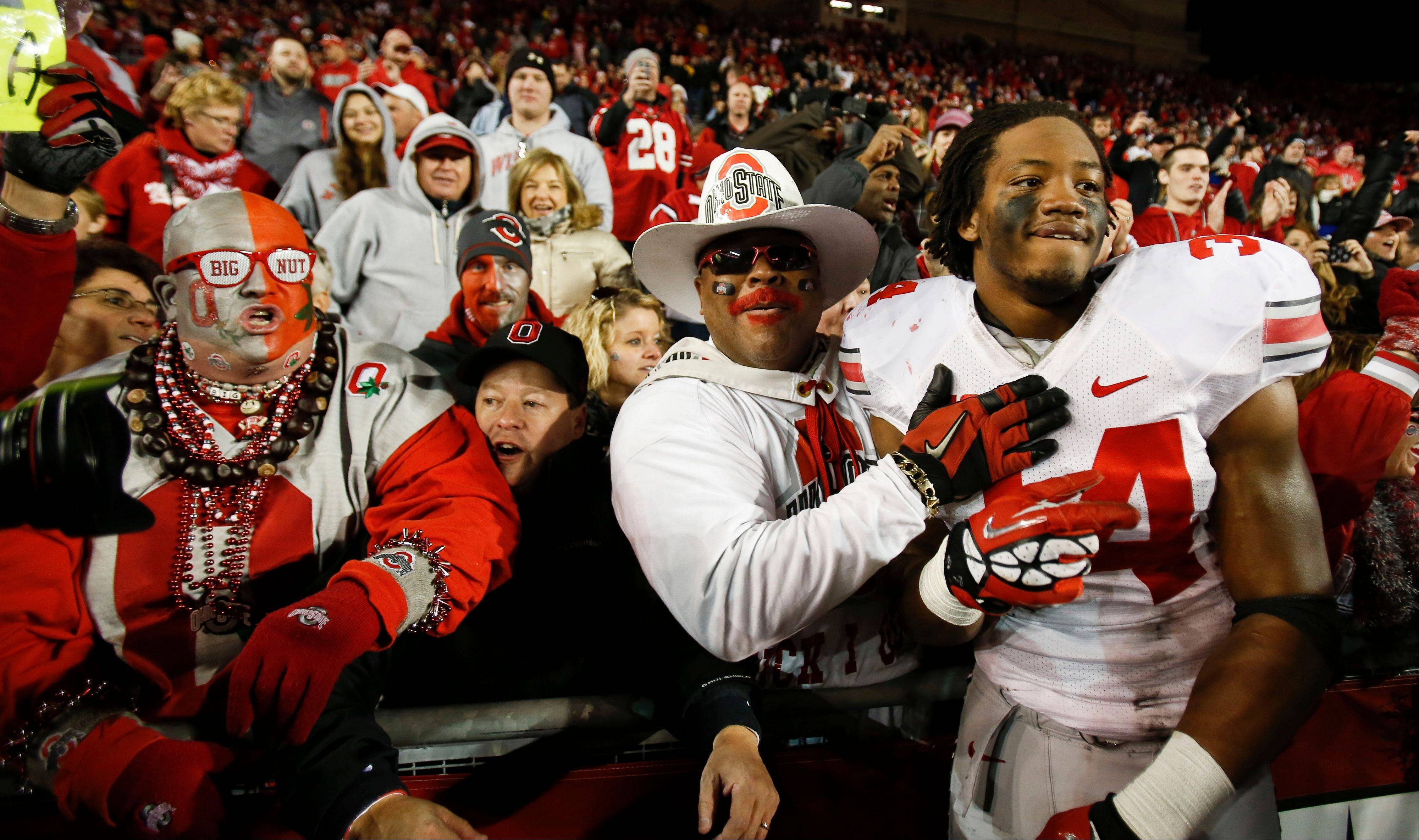 Ohio State fans celebrate Saturday with Carlos Hyde after the Buckeyes beat Wisconsin 21-14 in overtime in Madison, Wis. All that stands between the Buckeyes and a perfect season is archrival Michigan.