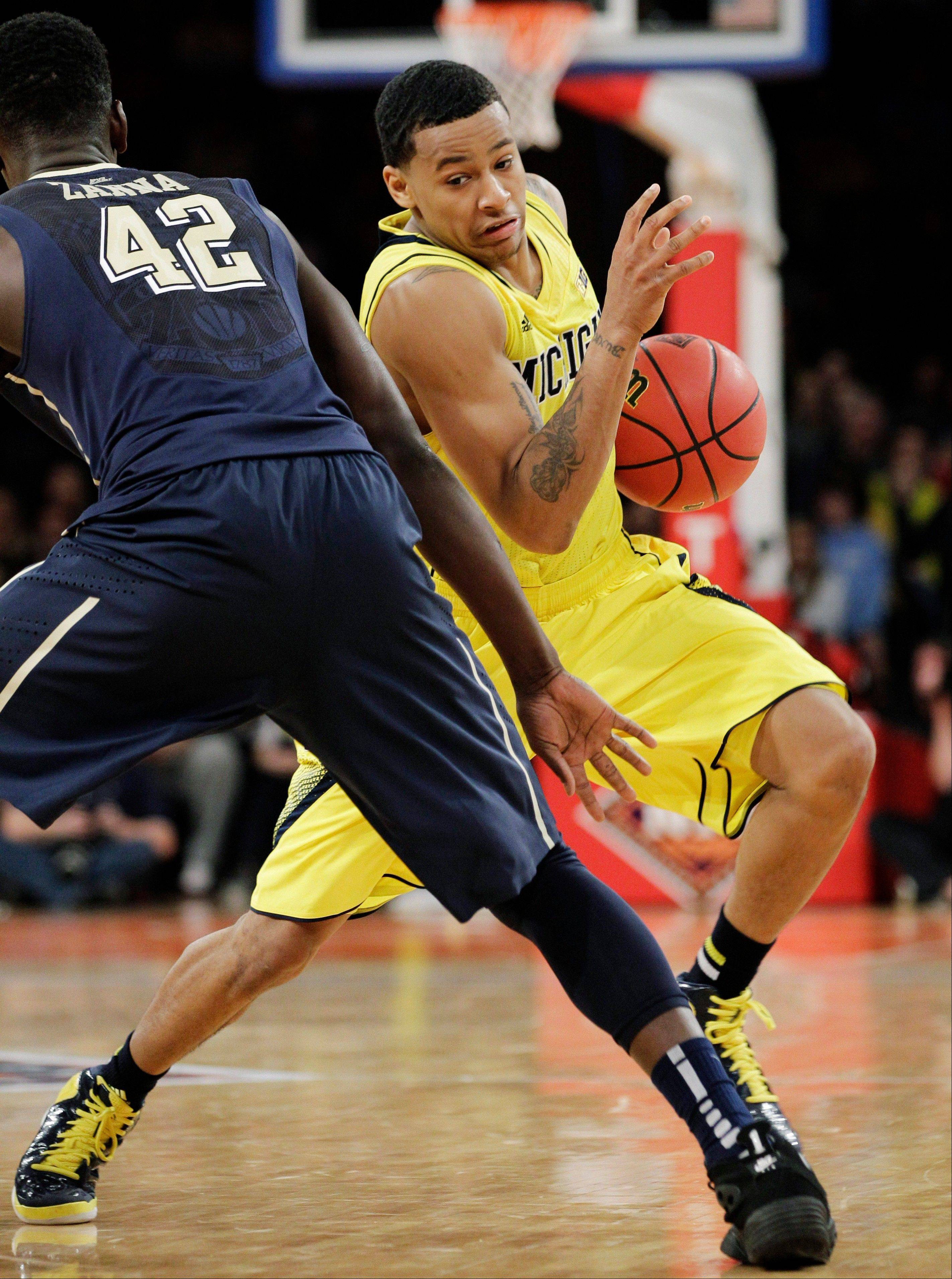 Michigan guard Trey Burke drives around Pittsburgh forward Talib Zanna in the first half Wednesday in the NIT Season Tip-Off at Madison Square Garden in New York.