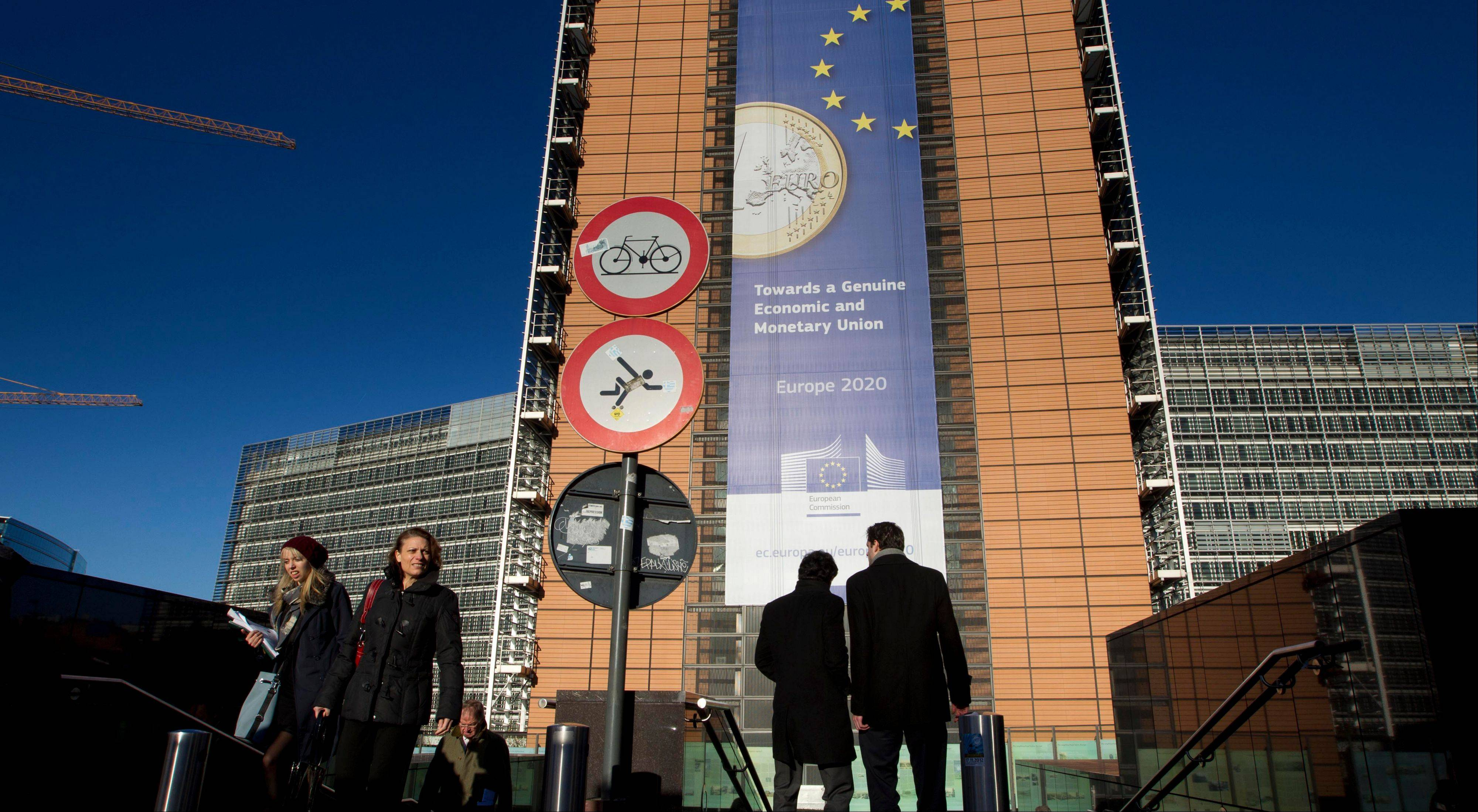 People walk in front of a giant banner for the euro currency outside of an EU summit in Brussels on Thursday, Nov. 22, 2012. Leaders from around Europe are arriving in Brussels Thursday for what promises to be a turbulent summit on the budget for the 27-country European Union. And for once, Britain will be at the heart of the debate.