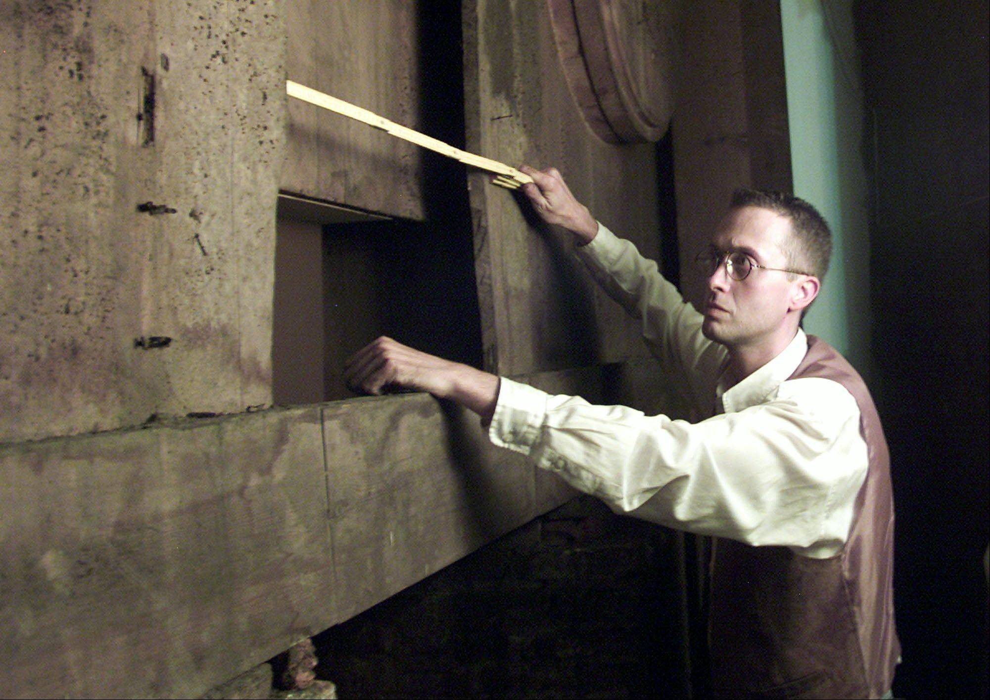 In this Oct. 4, 2002 file photo, police expert Jan Dekezel shows a hiding place behind the altar of the Saint Michael church in Wetteren, Belgium.