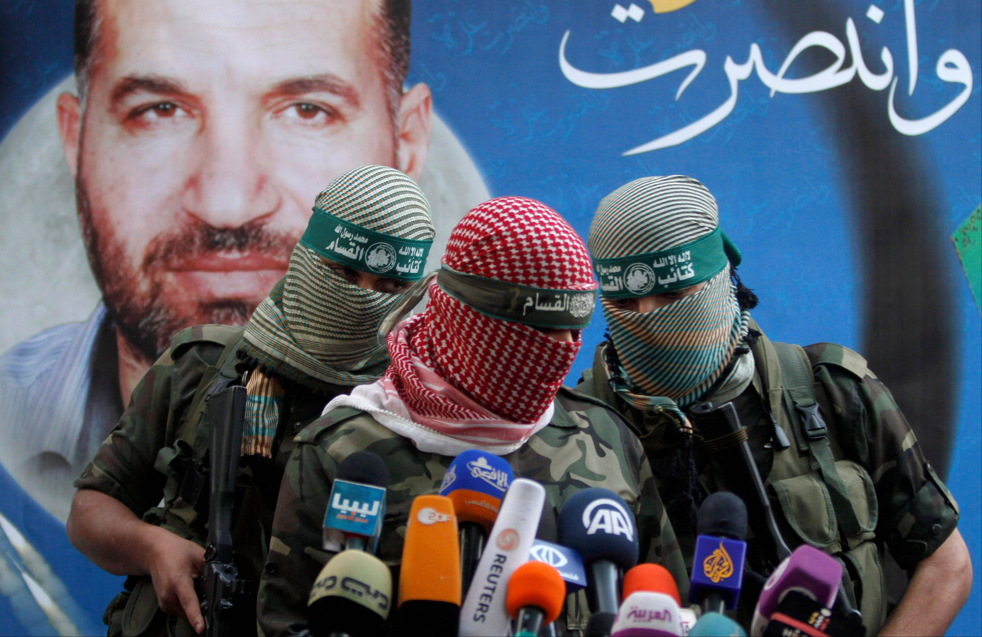 A Hamas militant talks during a press conference in Gaza City on Thursday. The poster in the background reads: �Gaza won� and shows the picture of Ahmed Jabari, a Hamas leader assassinated Nov.14 � the act that set off the last round of fighting between Israel and Hamas.