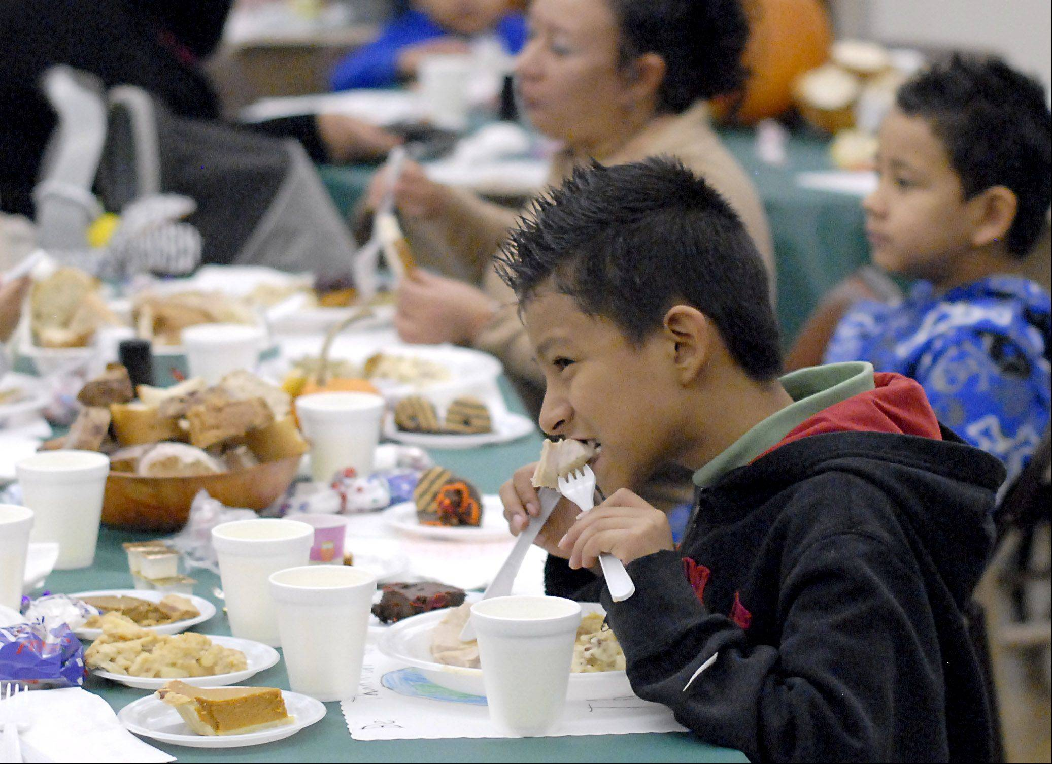 Daniel Lopez, 9, of Elgin chows down on a slice of turkey at Elgin�s fourth annual community dinner held Thursday for the first time at the First United Methodist Church. This is the third year his family has attended the gathering.